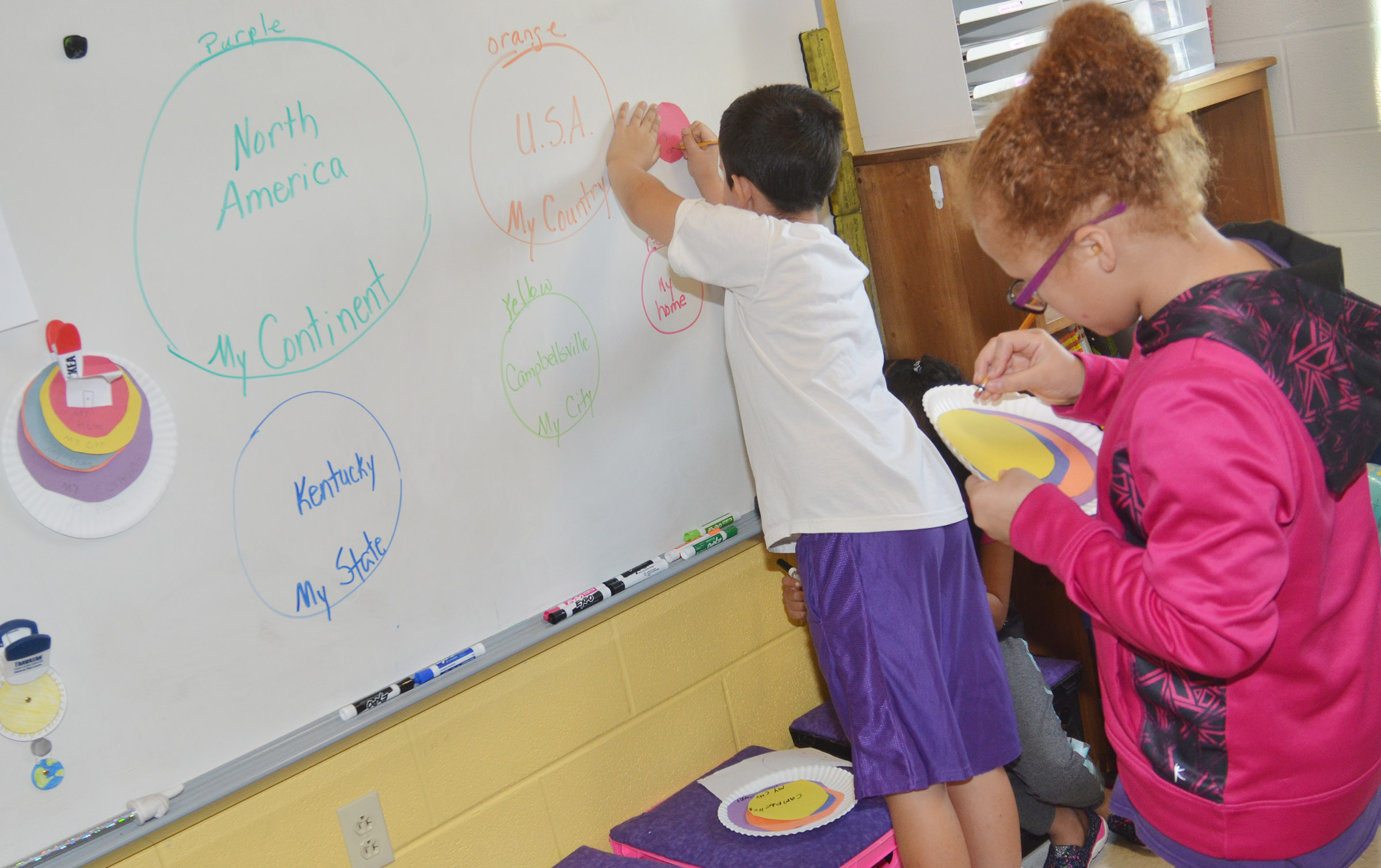 CES third-graders Damien Clark, at left, and Kallie Taylor write their absolute locations on their diagrams.