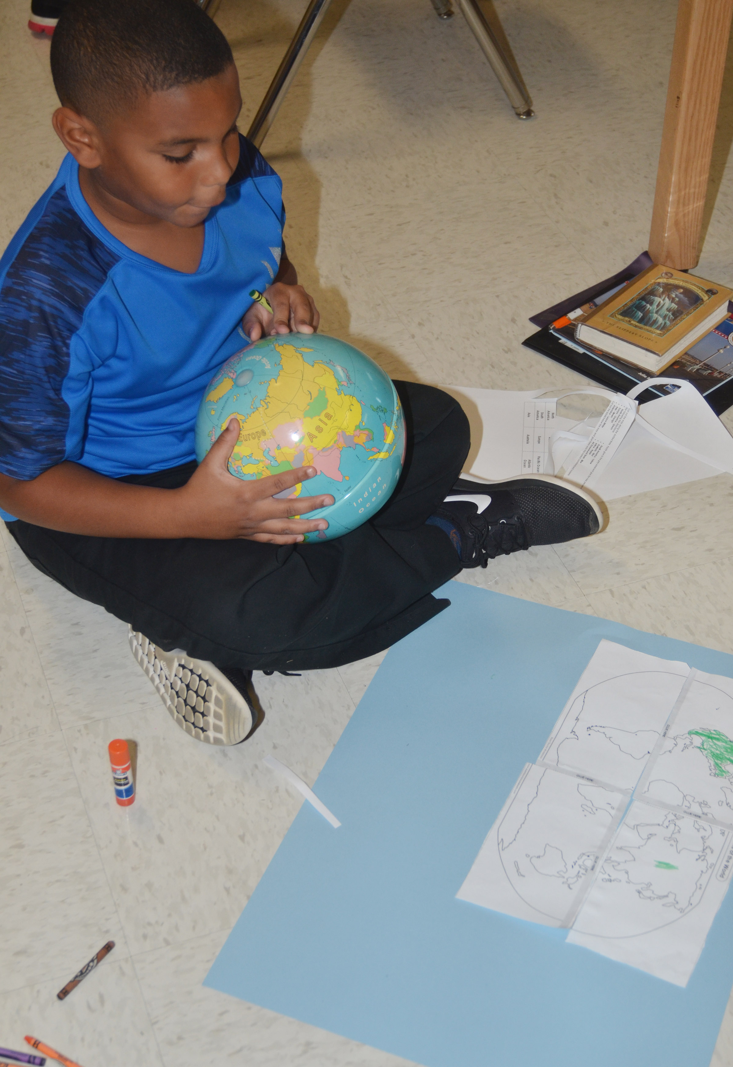 CES third-grader Zaemar Hoskins uses a globe to help him label the continents.