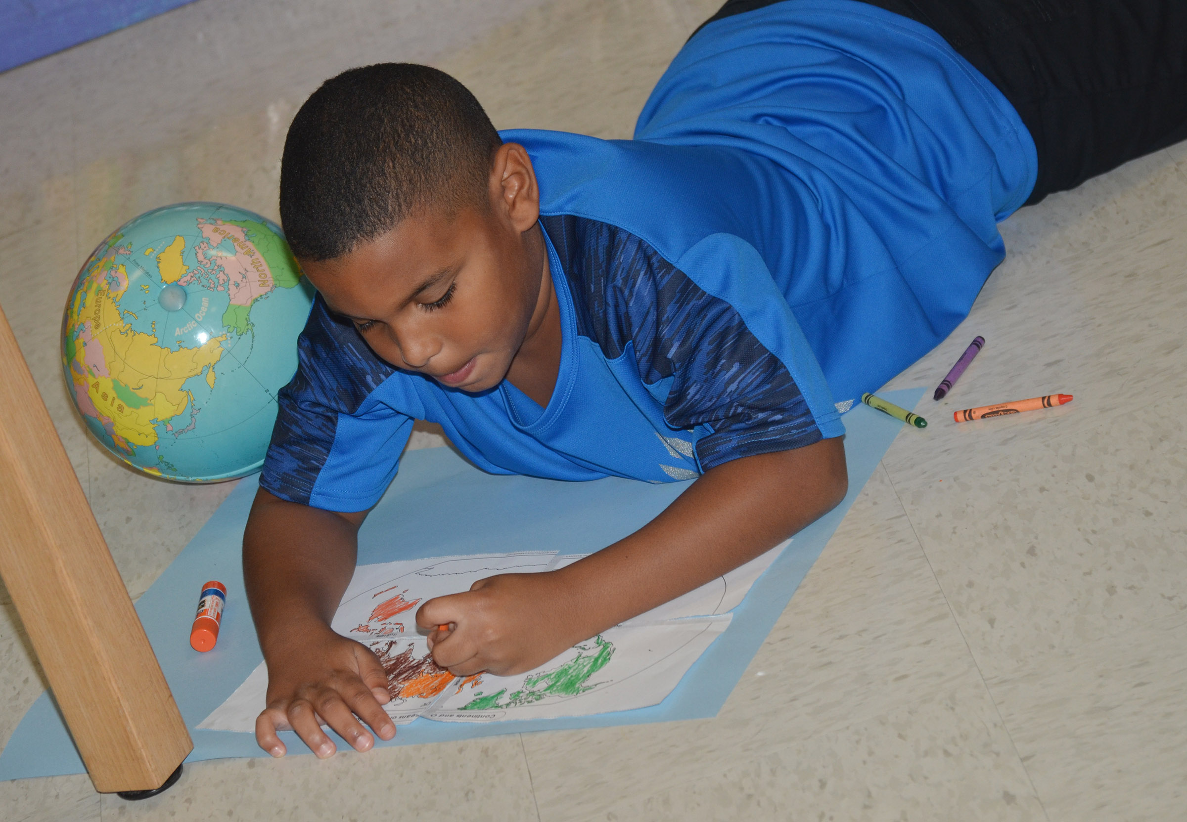 CES third-grader Zaemar Hoskins colors the continents.