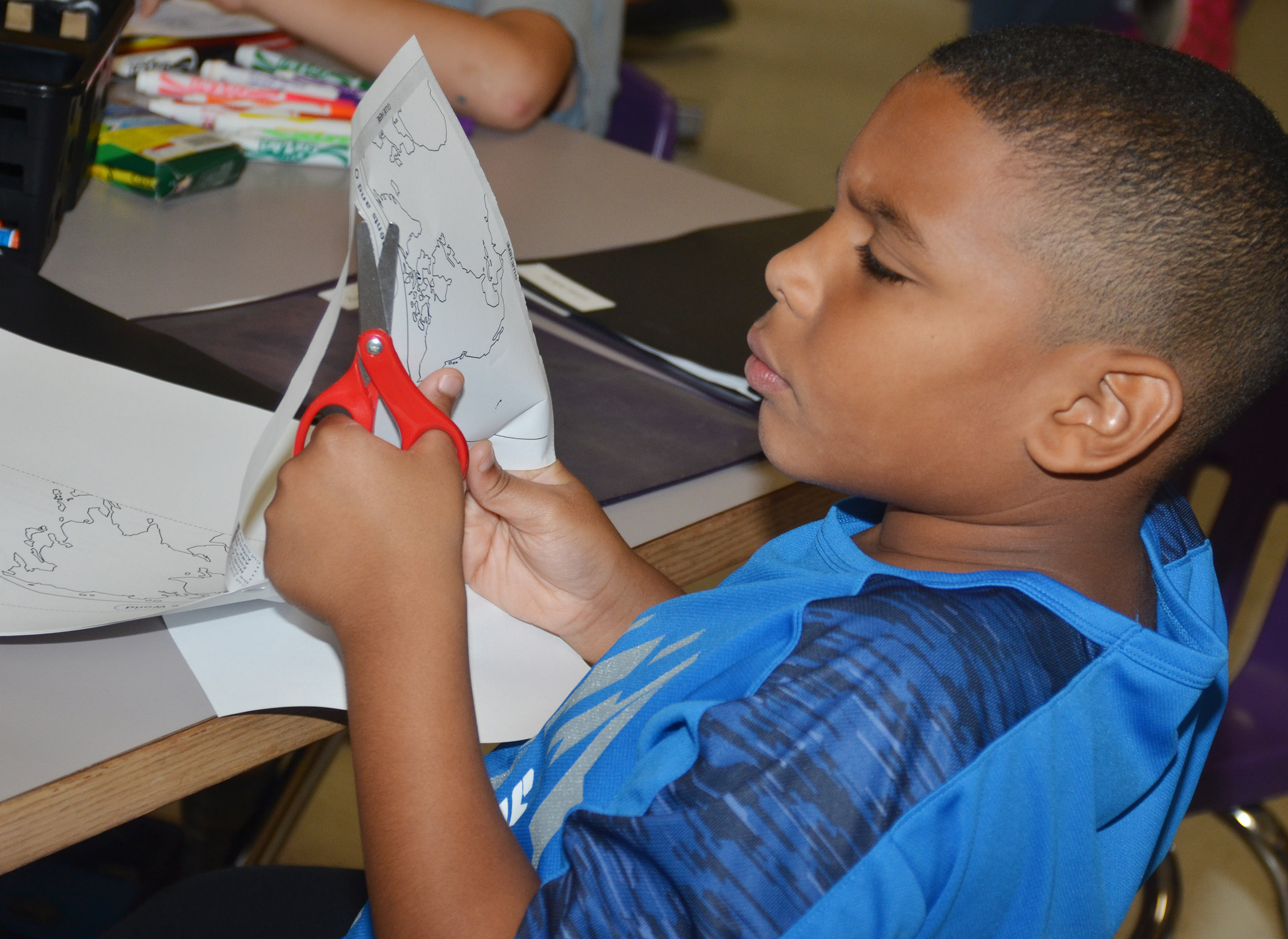 CES third-grader Zaemar Hoskins cuts out his continents to glue them on construction paper.