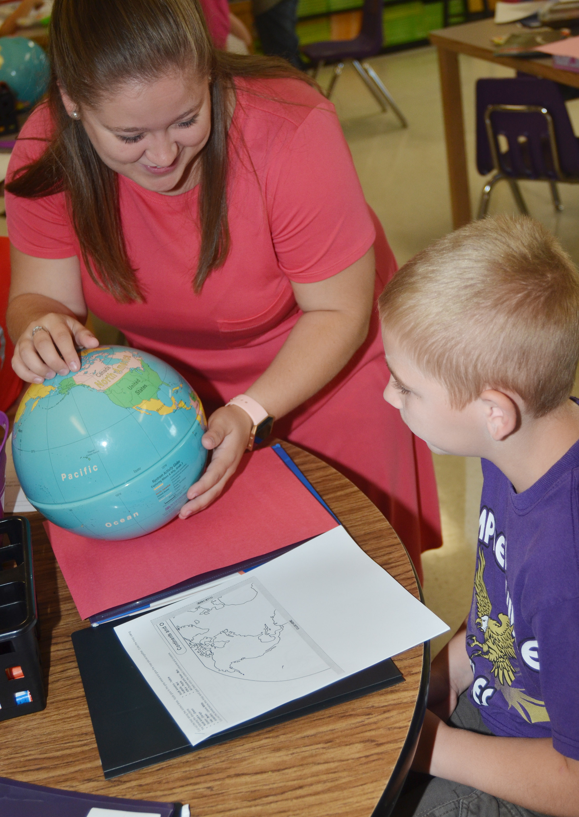 Campbellsville University education student Jordan Bray helps CES third-grader Joseph Greer identify the continents on a globe.