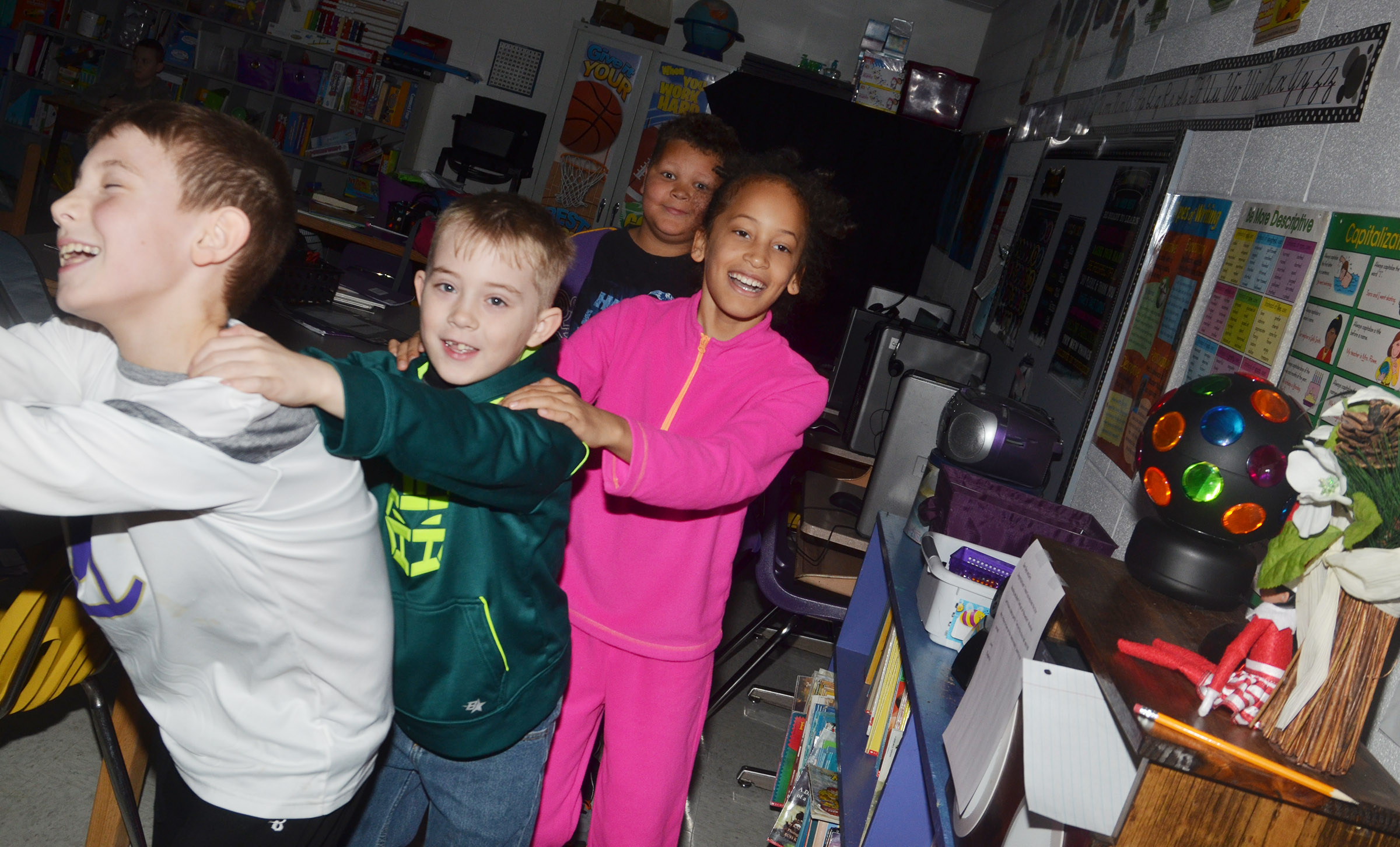 From left, CES third-graders Aidan Wilson, Devyn Tingle, Yazlyn Sutton and Drevonte Gurley dance with their classmates in a conga line during their disco party.