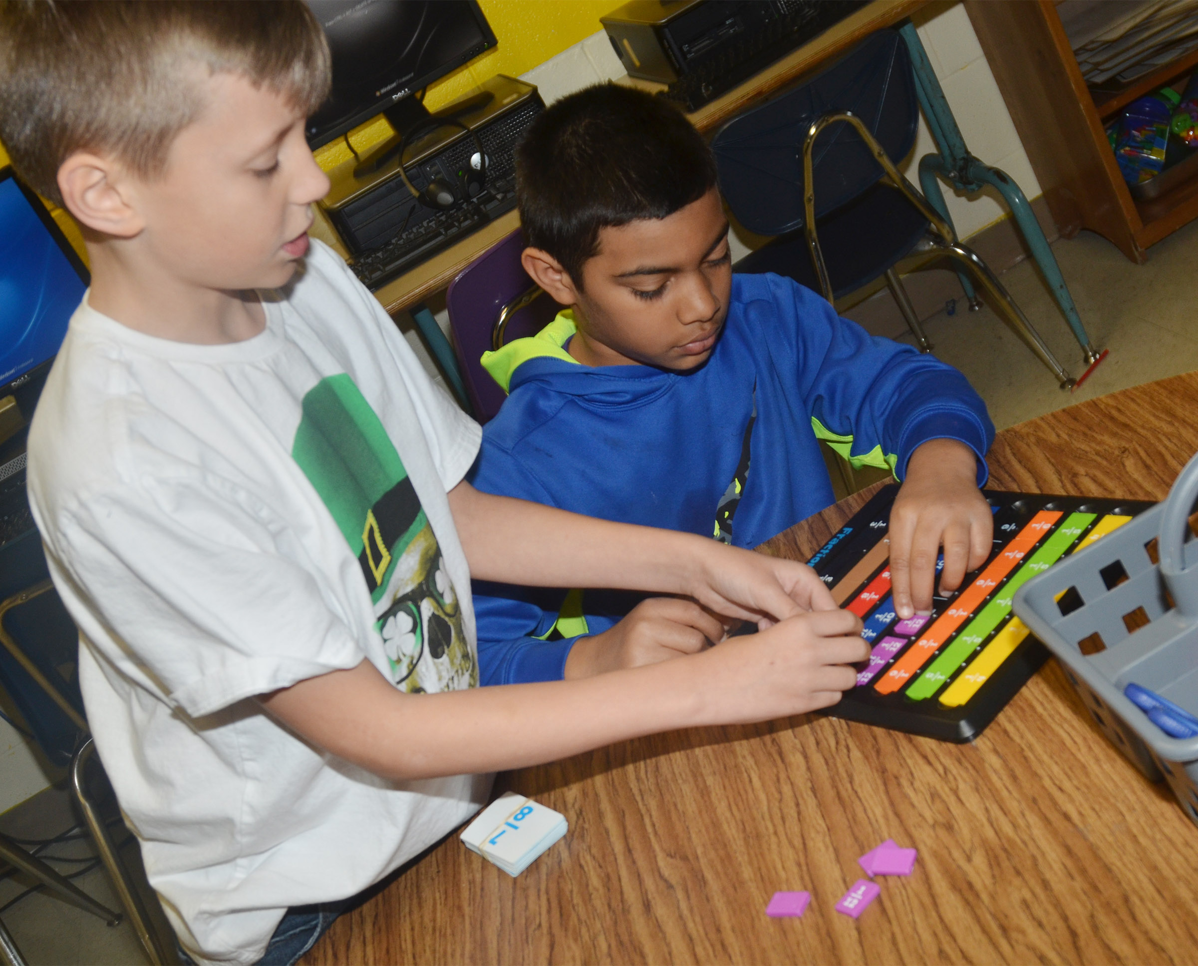 CES third-graders Cameron Taylor, at left, and LaDainien Smith use a math game to study fractions.