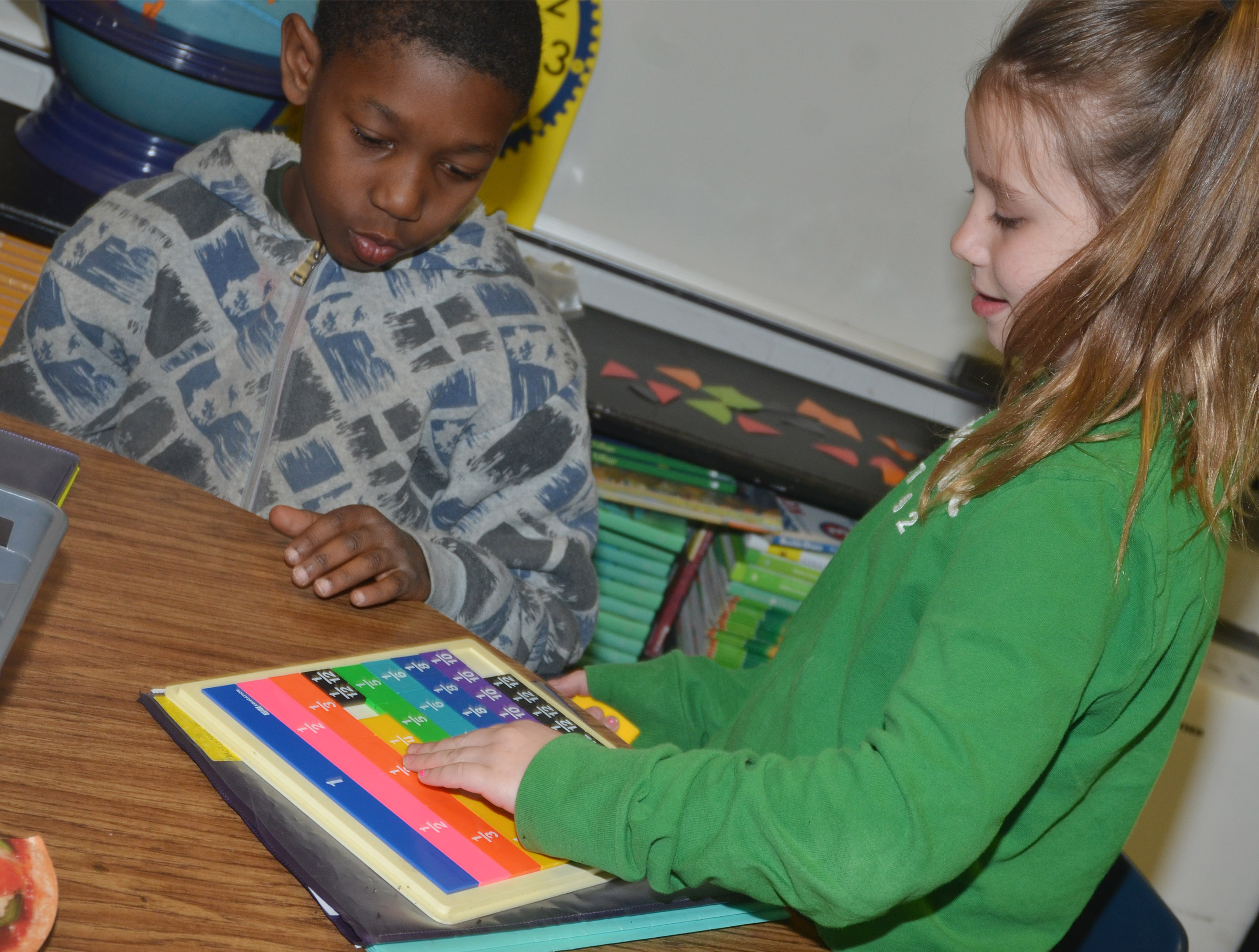 CES third-graders Jaron Johnson, at left, and McKailynn Grubaugh use a math game to study fractions.