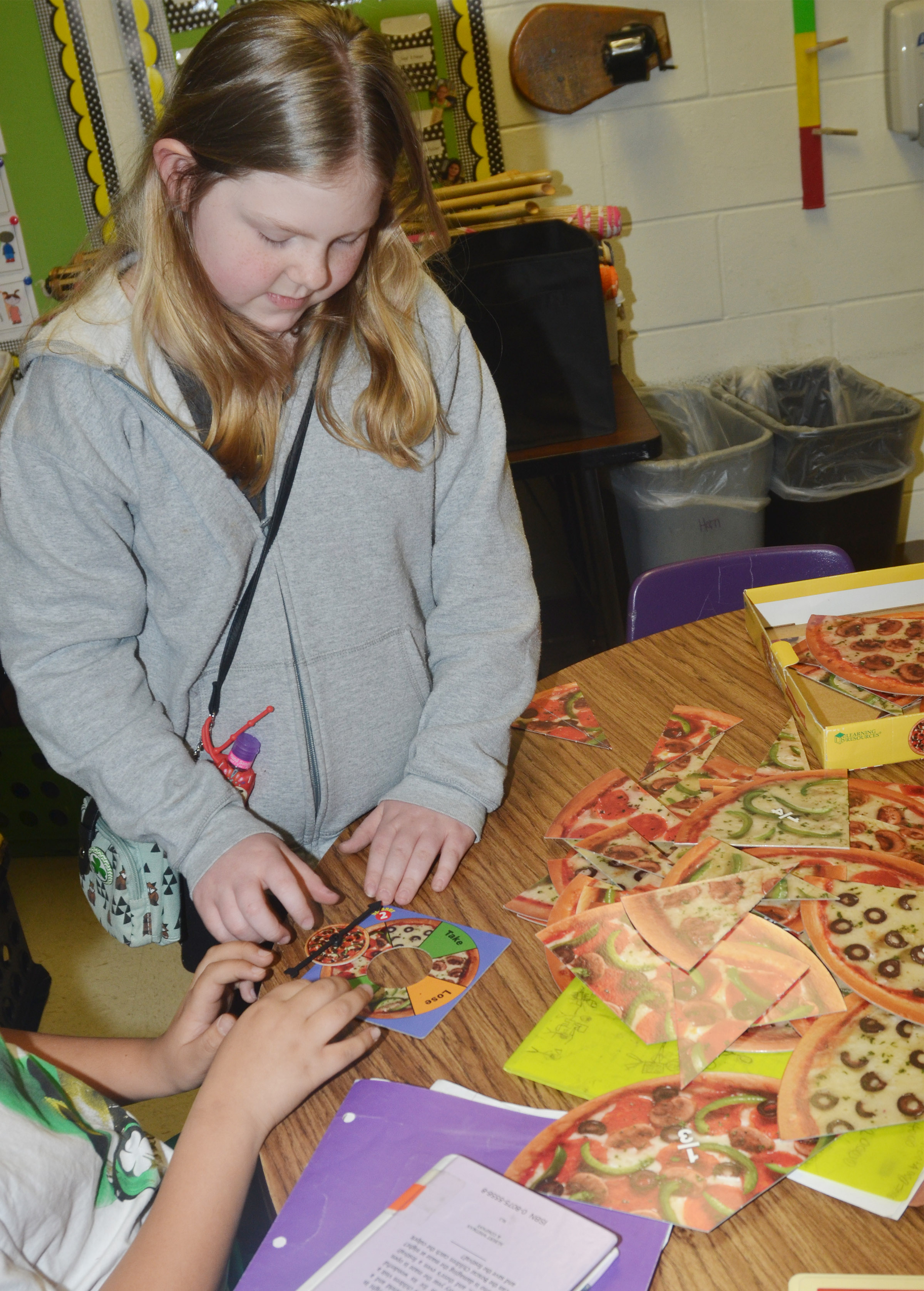 CES third-grader Alyssa Bennett and her classmates use a pizza game to study fractions.