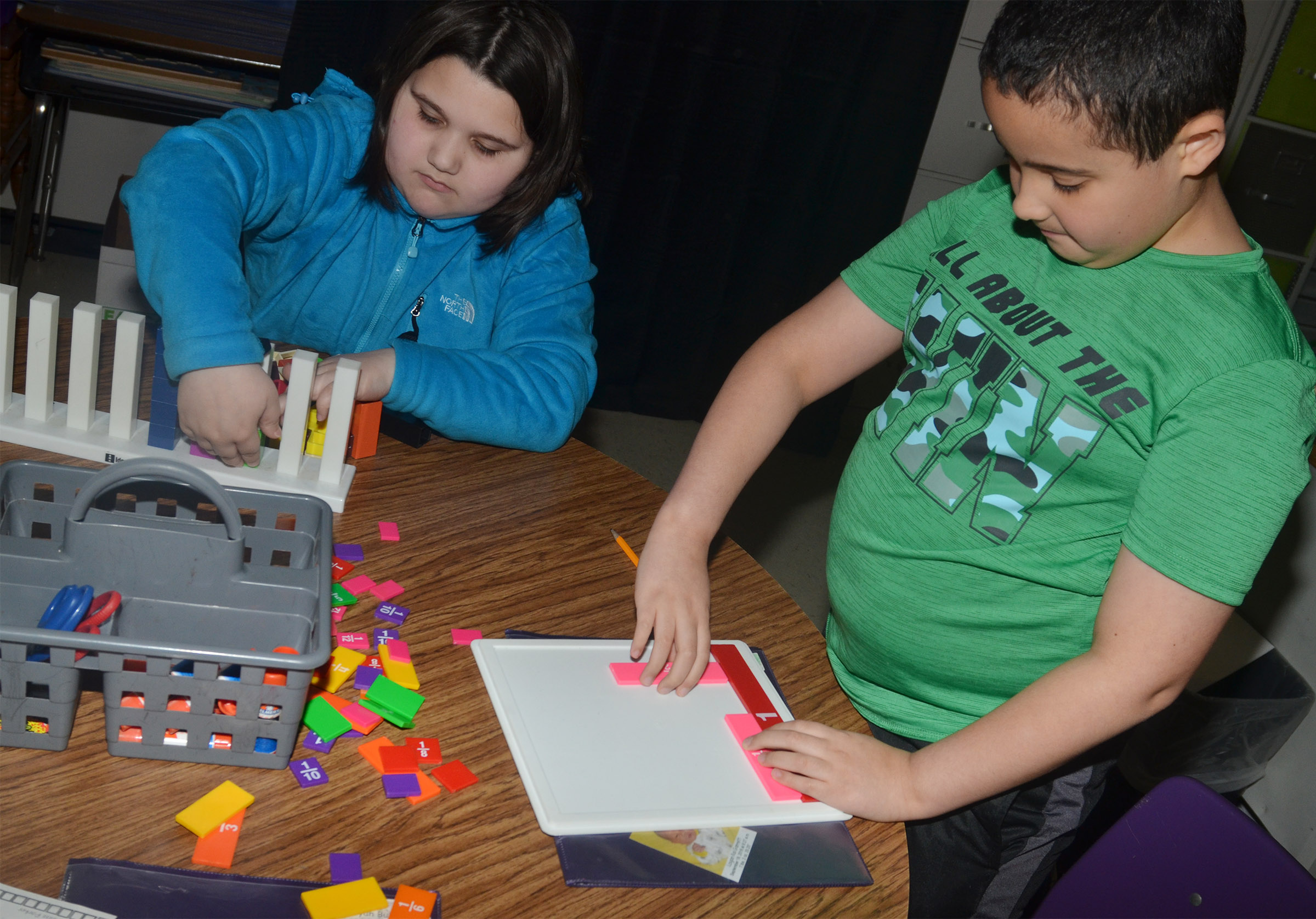 CES third-graders Kailei Hernandez, at left, and Tayshaun Hickman use blocks and a game to study fractions.