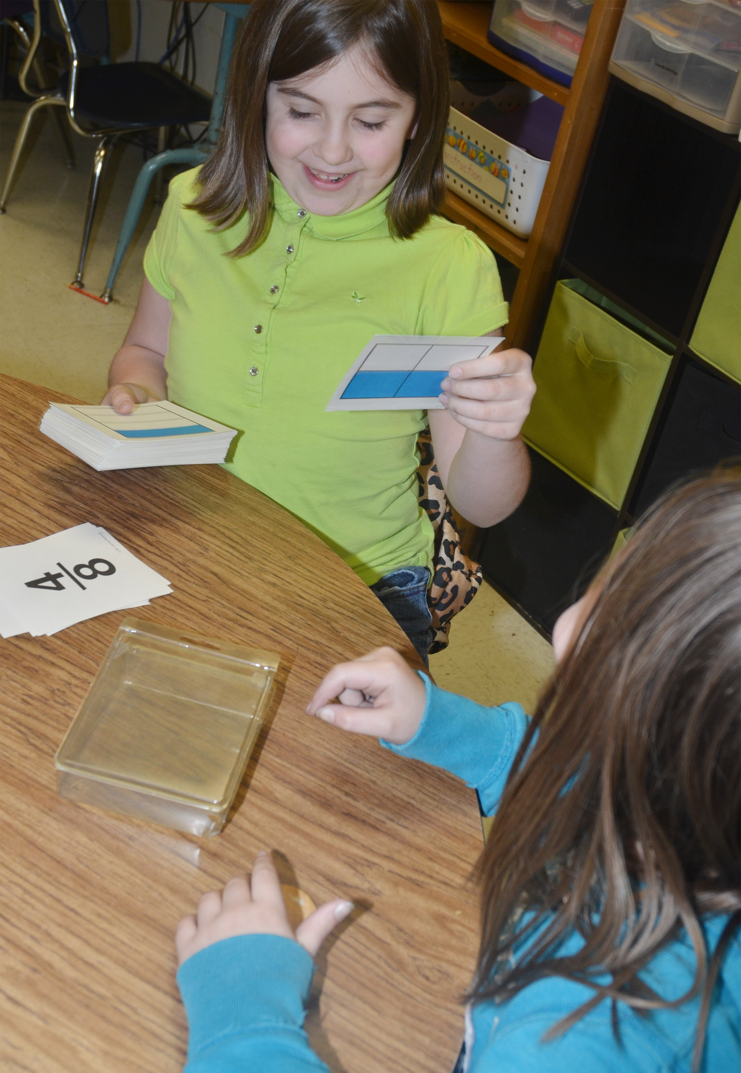CES third-graders Adrianna Garvin, at left, plays a flashcard game with Chloe Bates to study fractions.