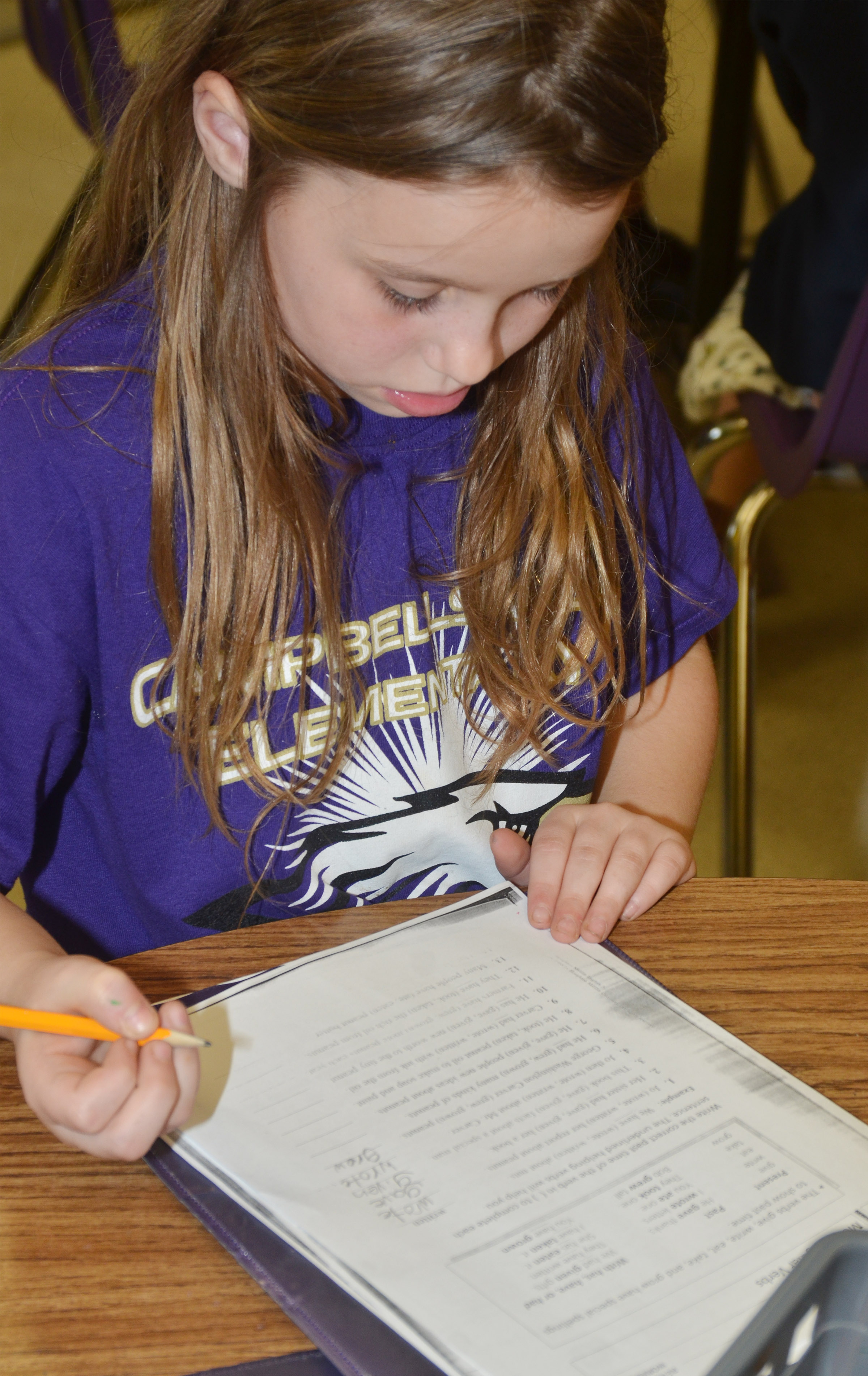 CES third-grader McKailynn Grubaugh completes her irregular verb worksheet.