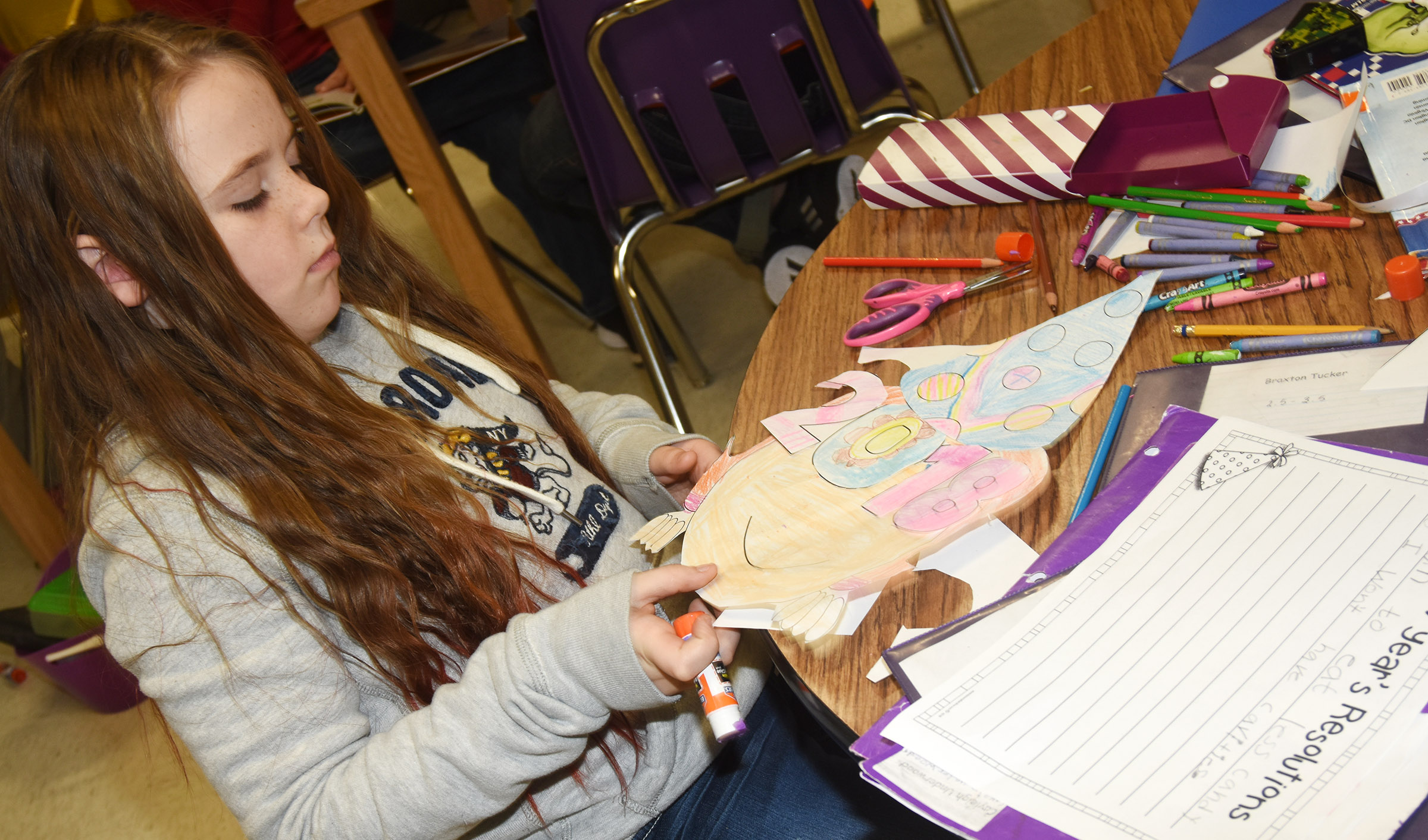 CES third-grader Cayleigh Underwood glues together her New Year's resolution project.