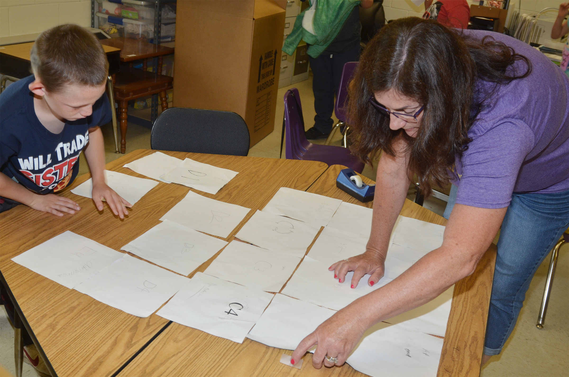 CES third-grade teacher Patty Haley and Cohutta Giles tape the class puzzle together.