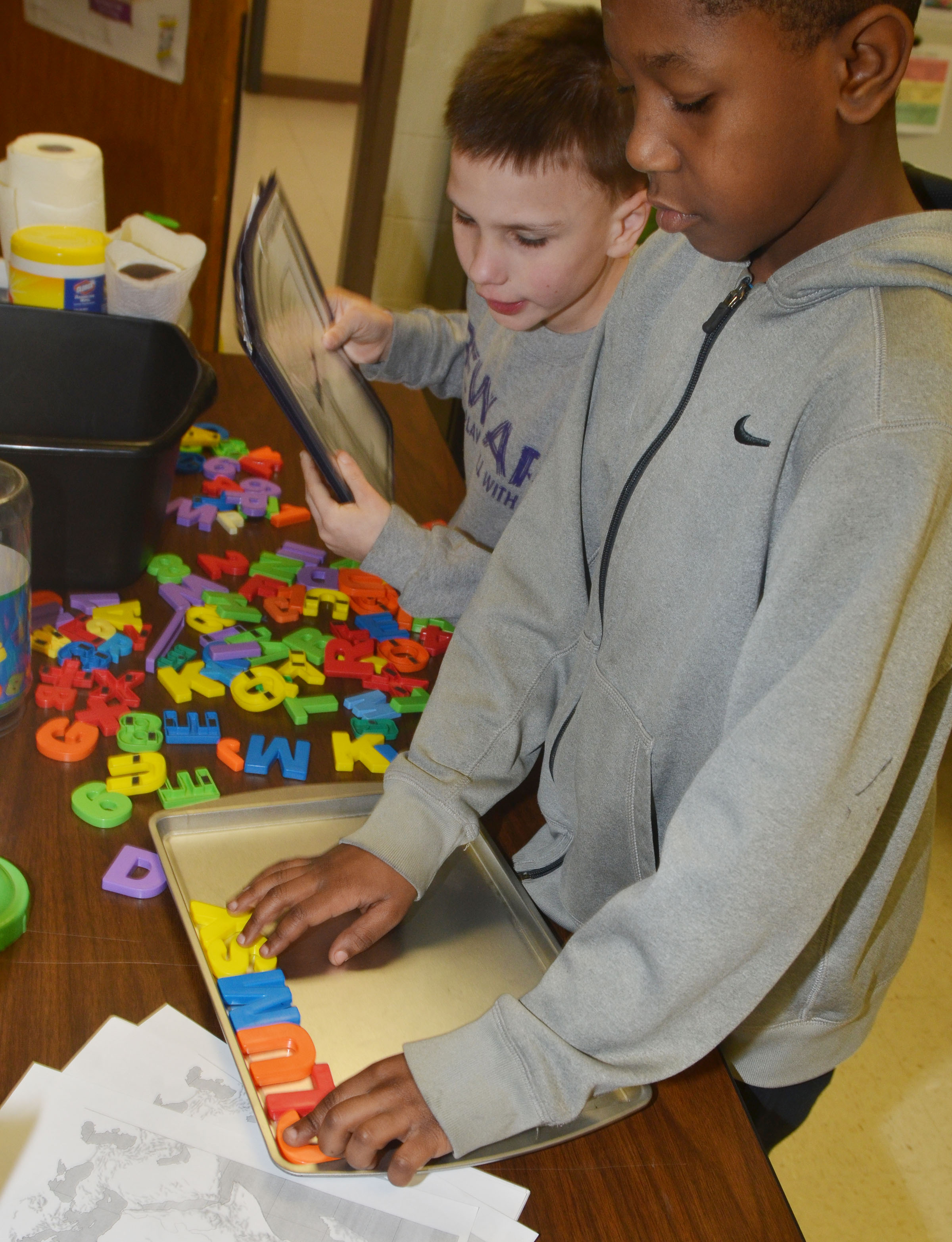 CES third-graders Jayden Harris, at left, and Jaron Johnson practice spelling sight words with magnetic letters and a cookie sheet.