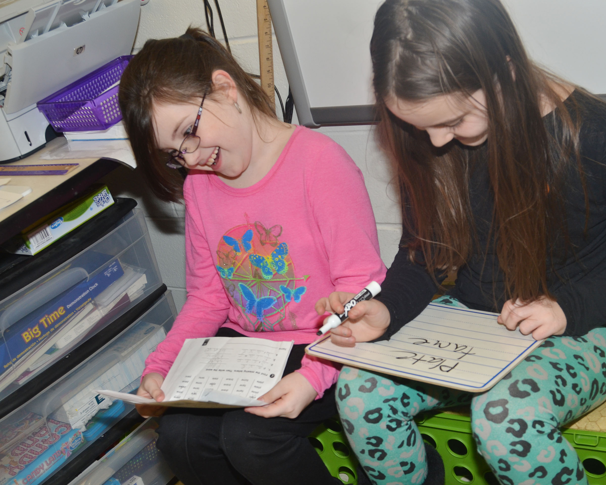 CES third-graders Lauren Pace, at left, and Alexis Roddy practice writing their sight words with dry erase markers and a board.