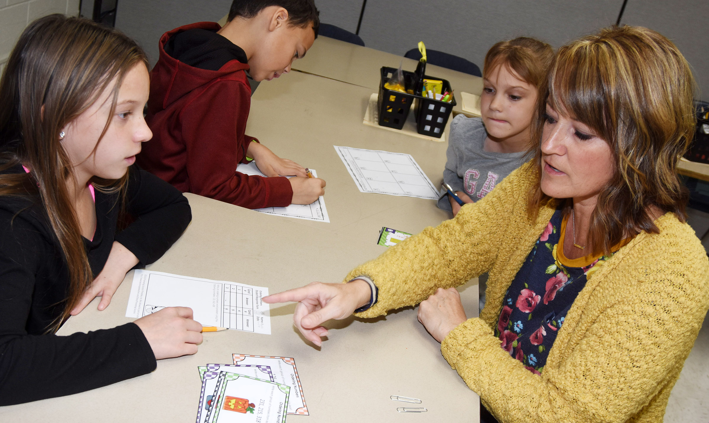 CES math interventionist Vanessa Adkins helps fourth-grader Alyah Meadows play a number order game.