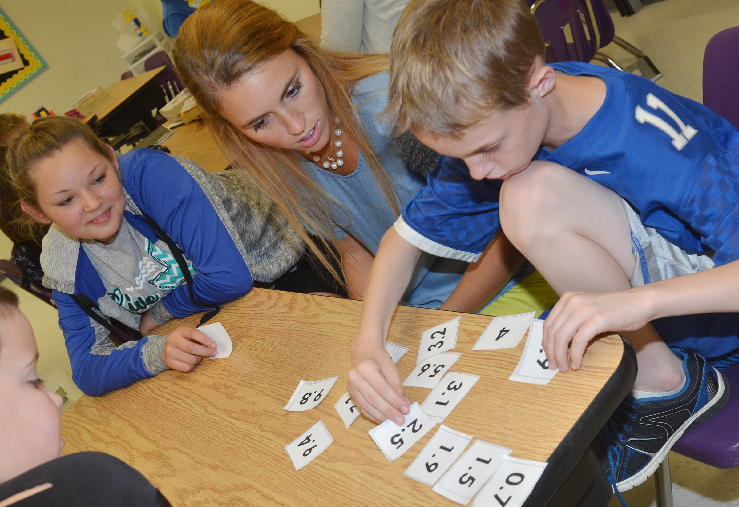 CES student teacher LeeAnn Grider helps fifth-grader Piper Maggard, at left, and Will Wooley place numbers in order.