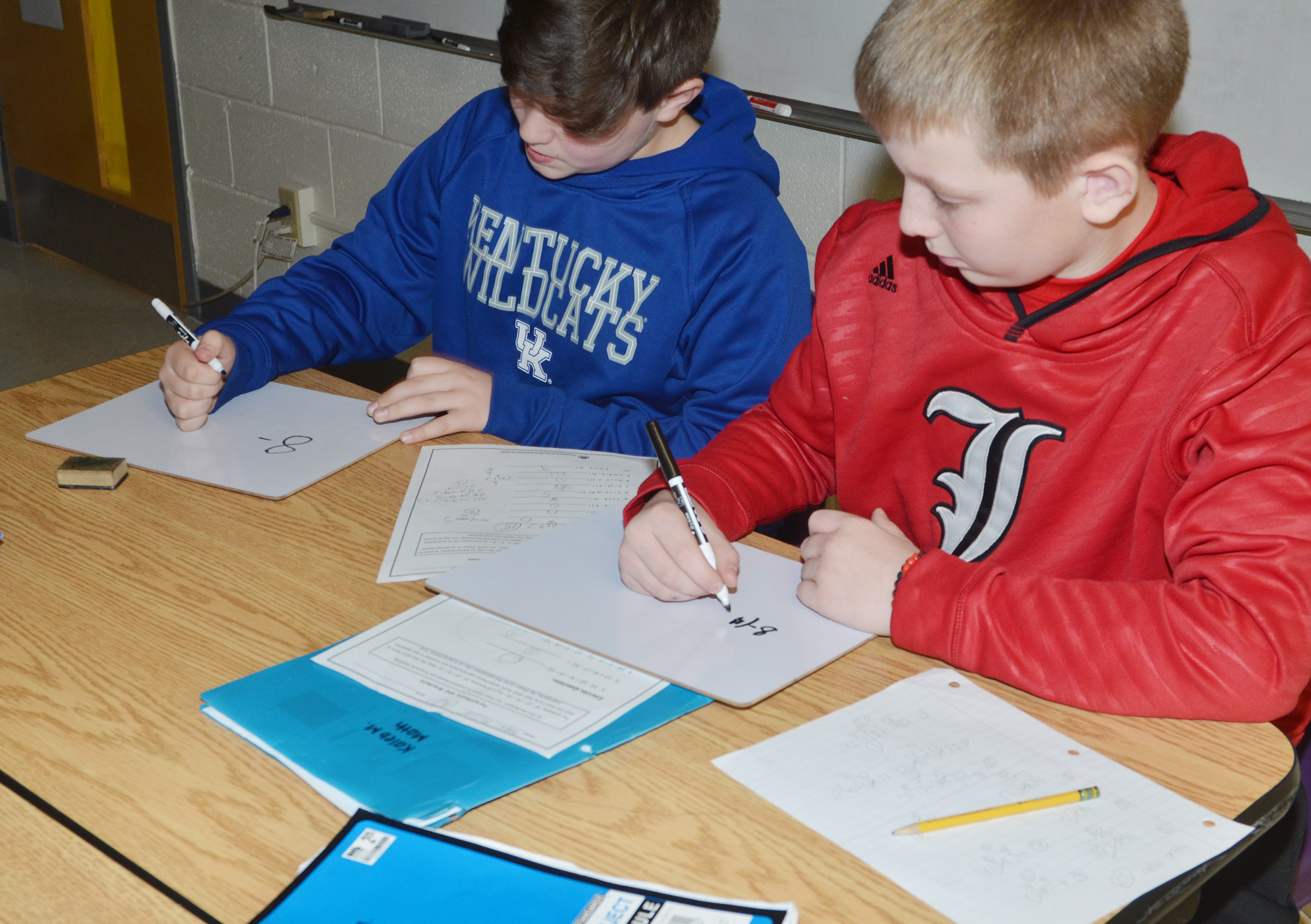 CES fifth-graders Andrew Mardis, at left, and Kaleb Miller work together to write a mathematical problem.