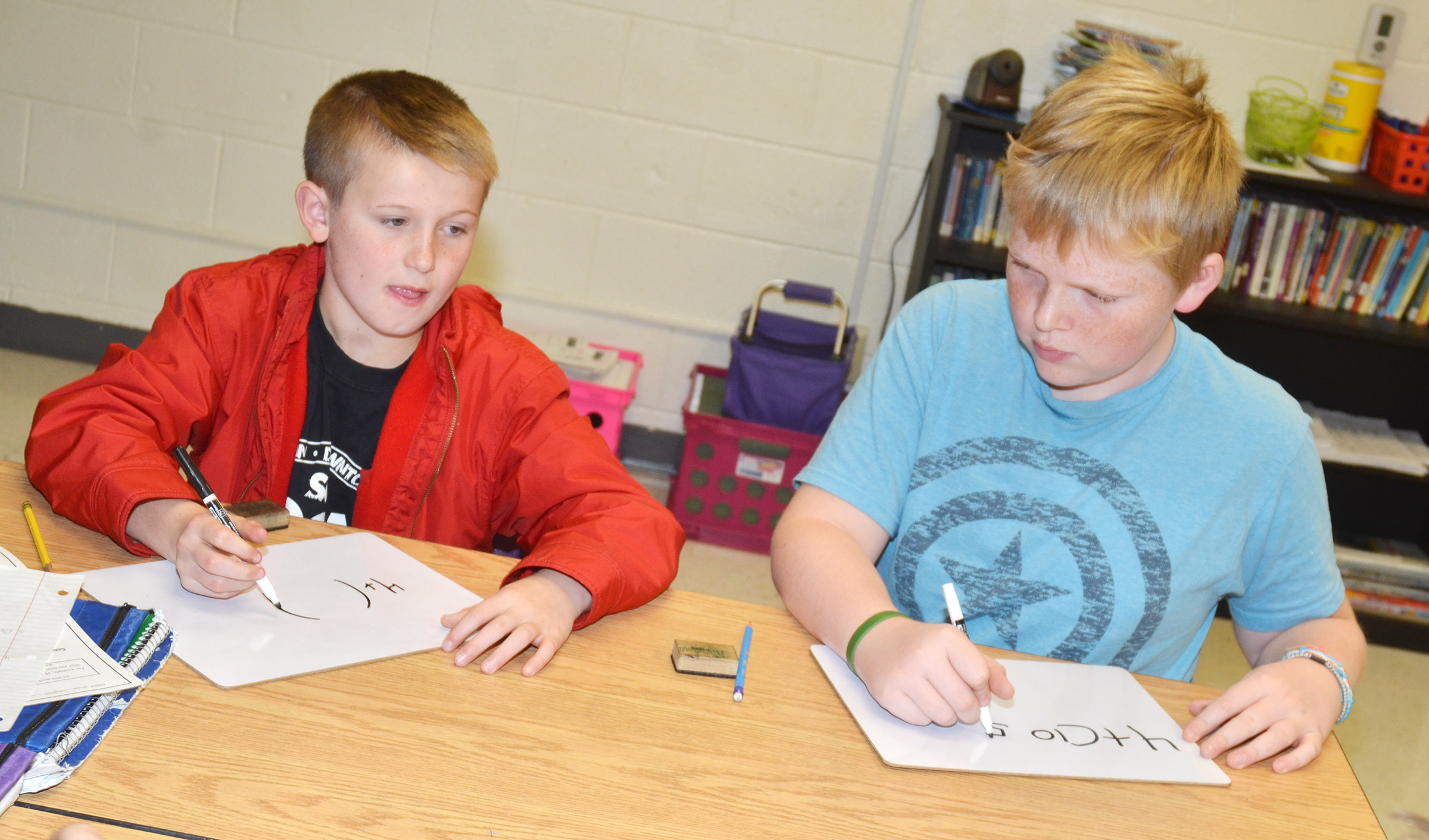 CES fifth-graders Arthur Singleton, at left, and Simon Wilkerson work together to write a mathematical problem.