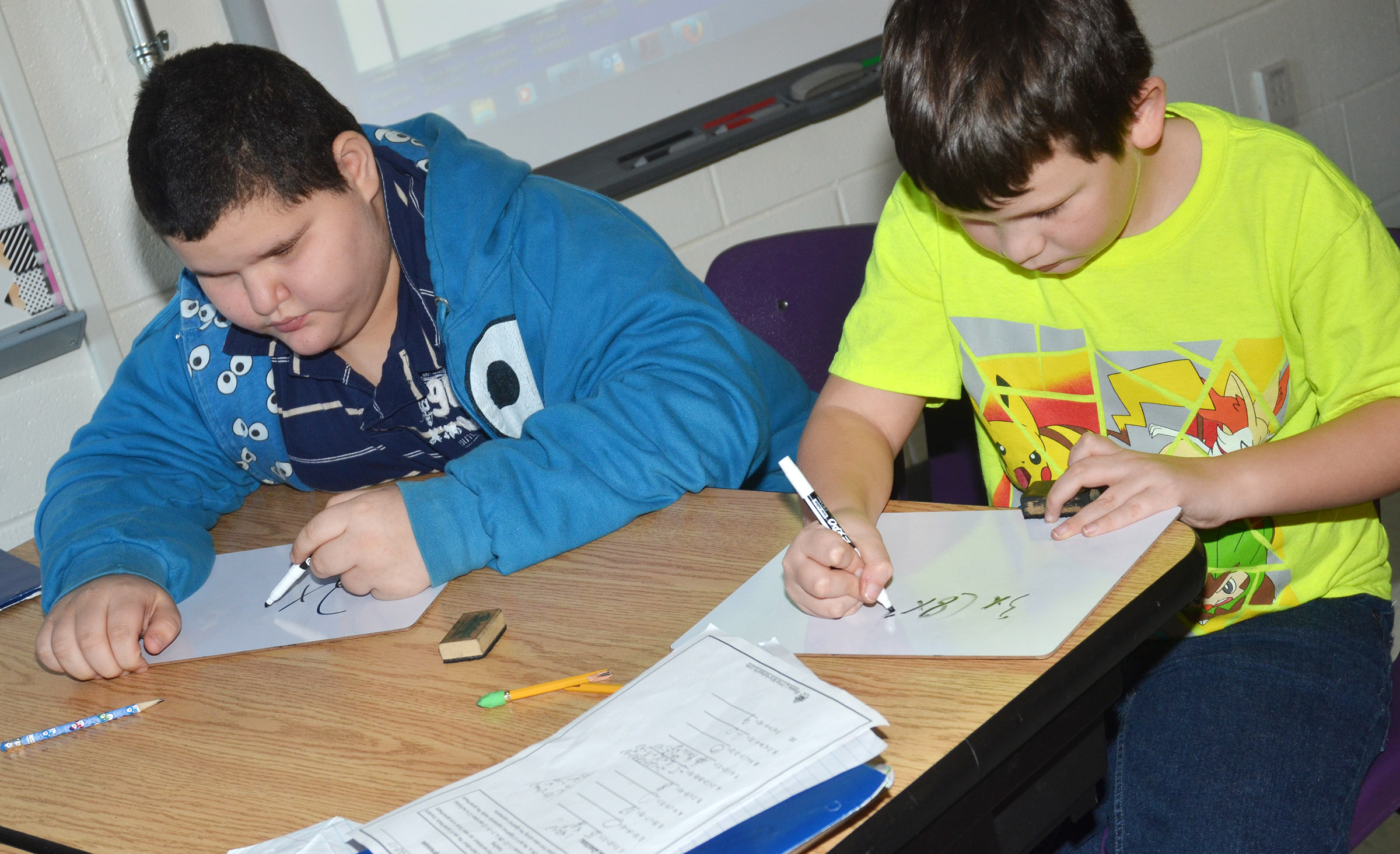 CES fifth-graders Steven Miller, at left, and Mason Fisher write a mathematical problem.