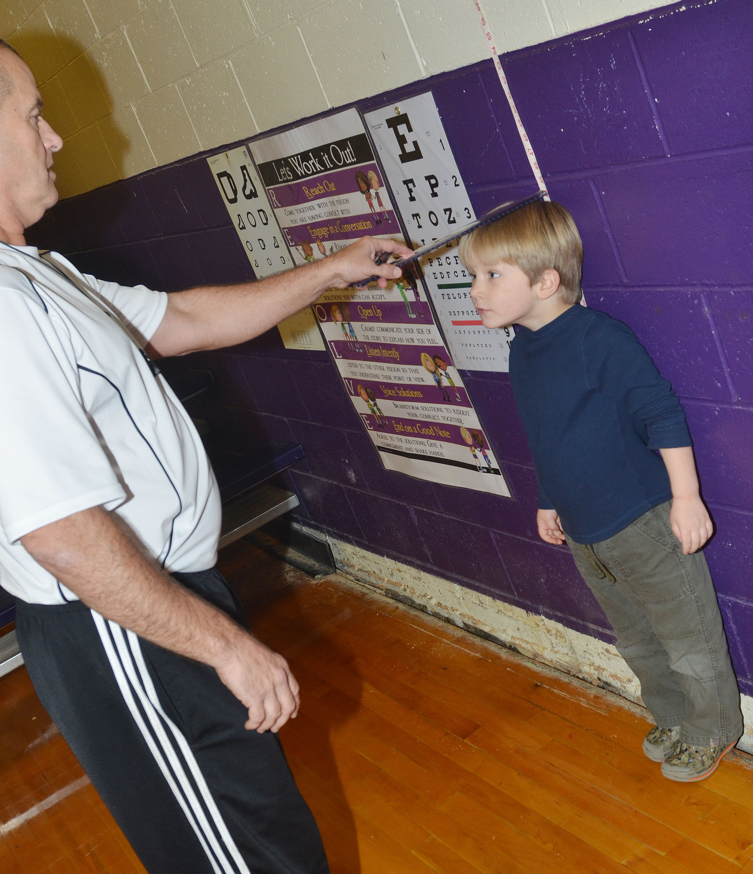 CES kindergartener Luke Banta stands tall as physical education teacher Lynn Kearney measures his height.