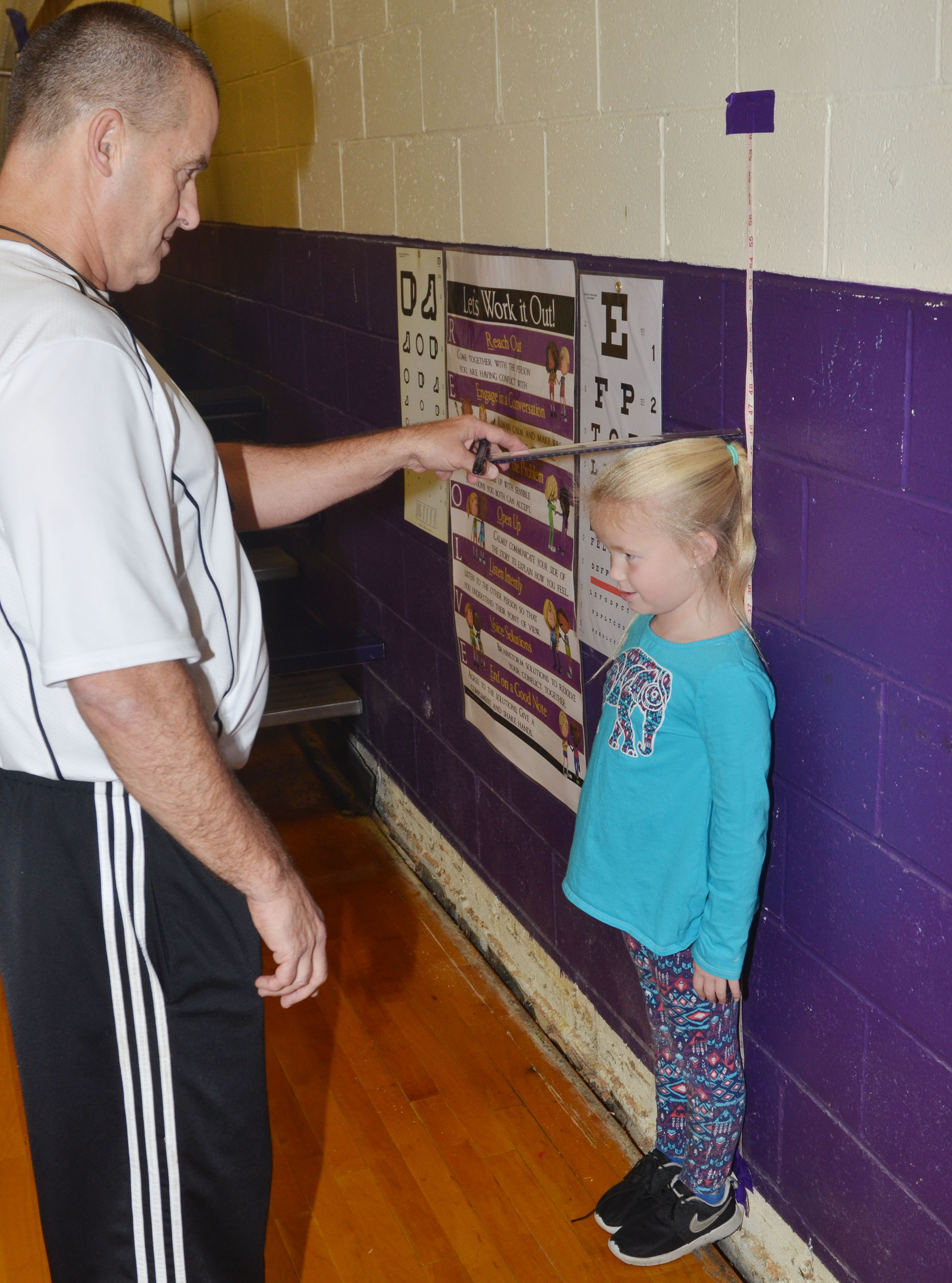 CES kindergartener Lillie Judd stands still as physical education teacher Lynn Kearney measures her.