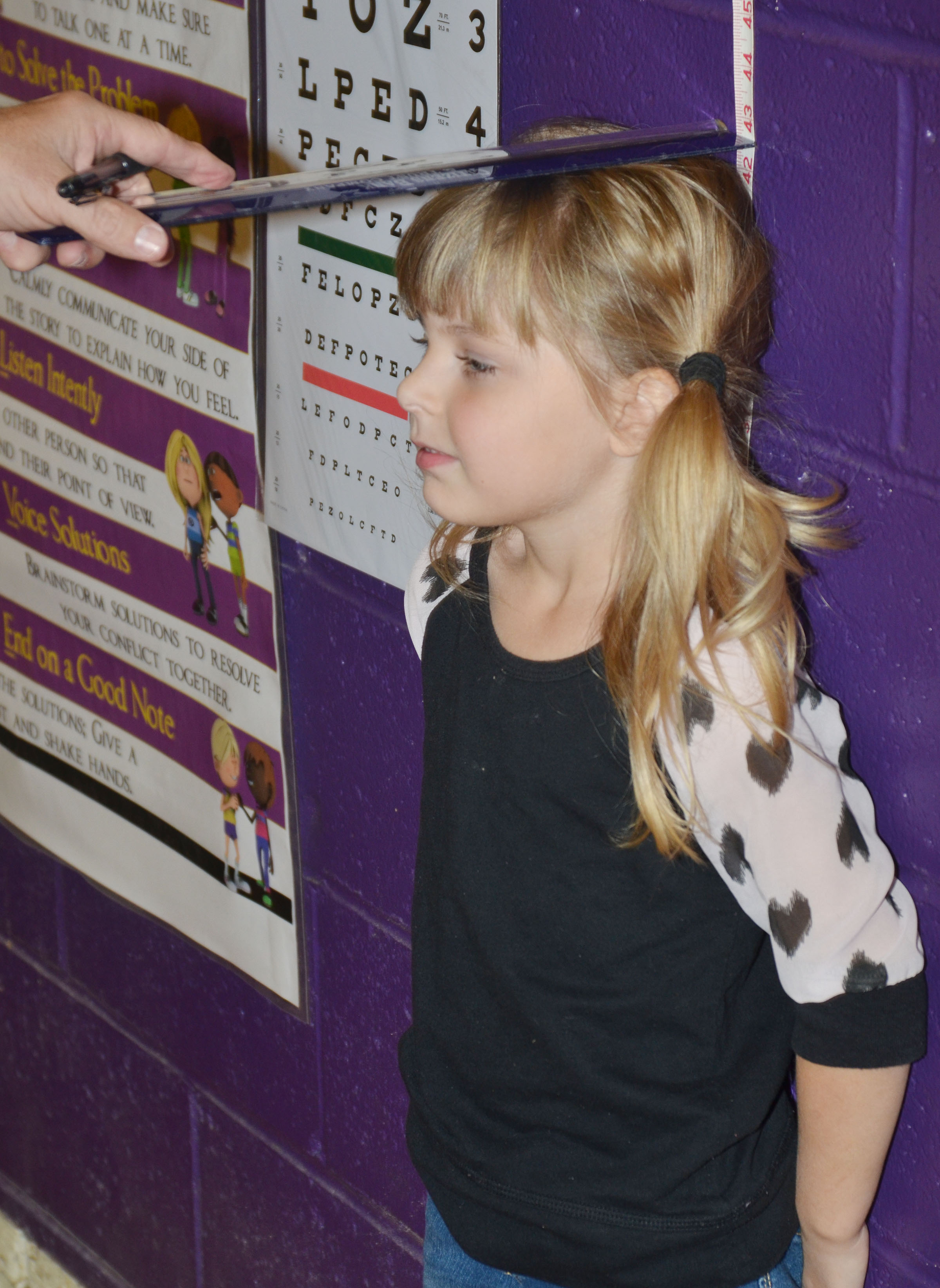 CES kindergartener Madison Wilhoite stands still as physical education teacher Lynn Kearney measures his height.