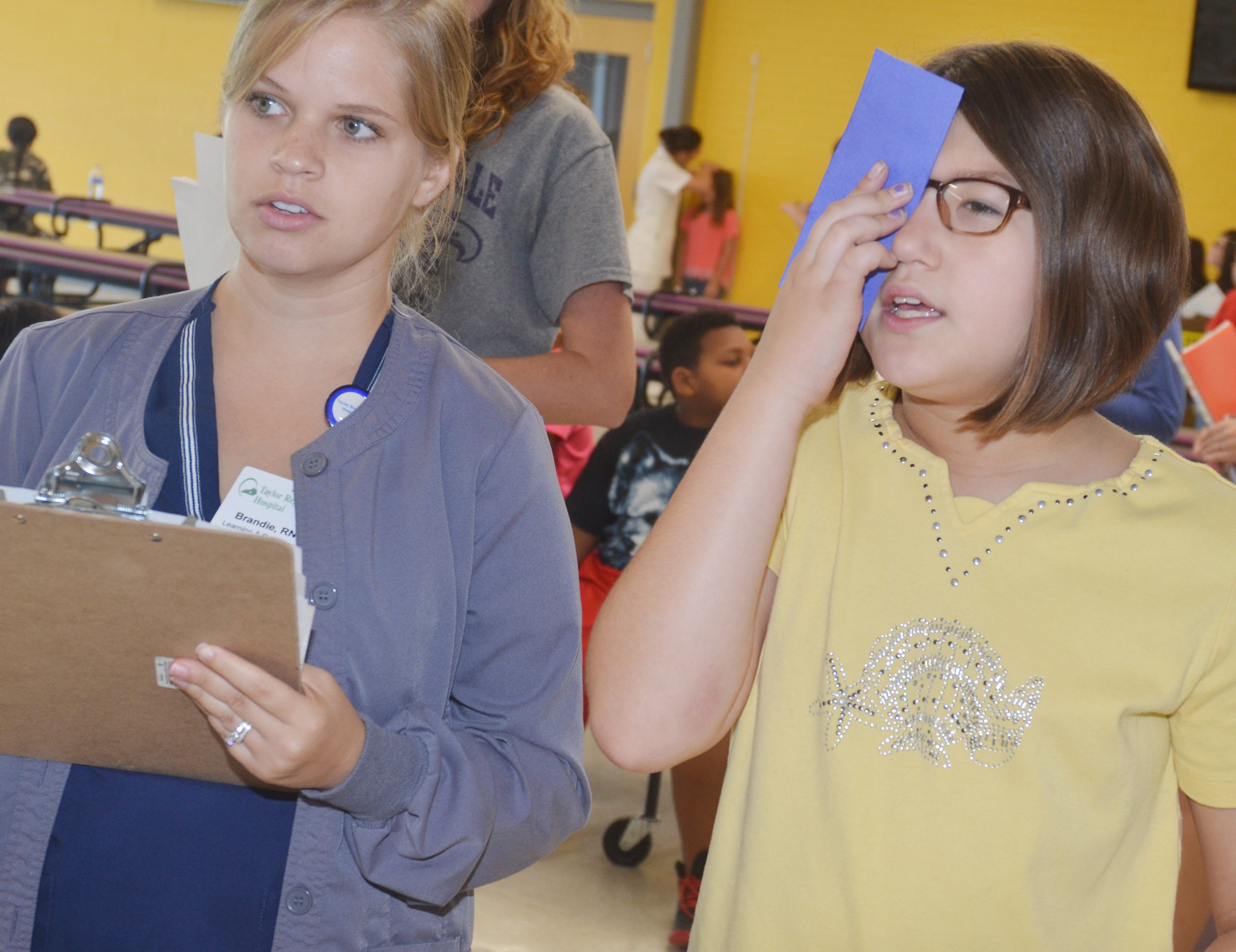 CES fifth-grader Kylee Sowders undergoes an eye exam with Brandie Adams, a registered nurse at Taylor Regional Hospital.
