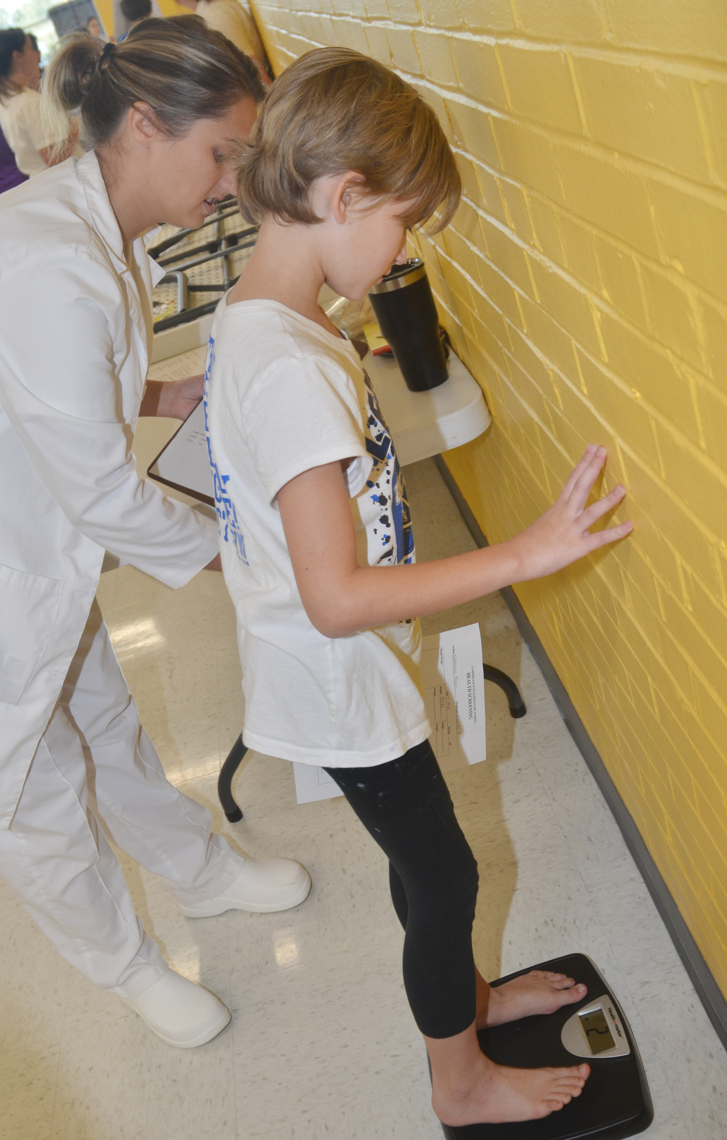 CES fourth-grader Katie Nunn weighs herself, with help from Campbellsville University nursing student Allie Stevens.