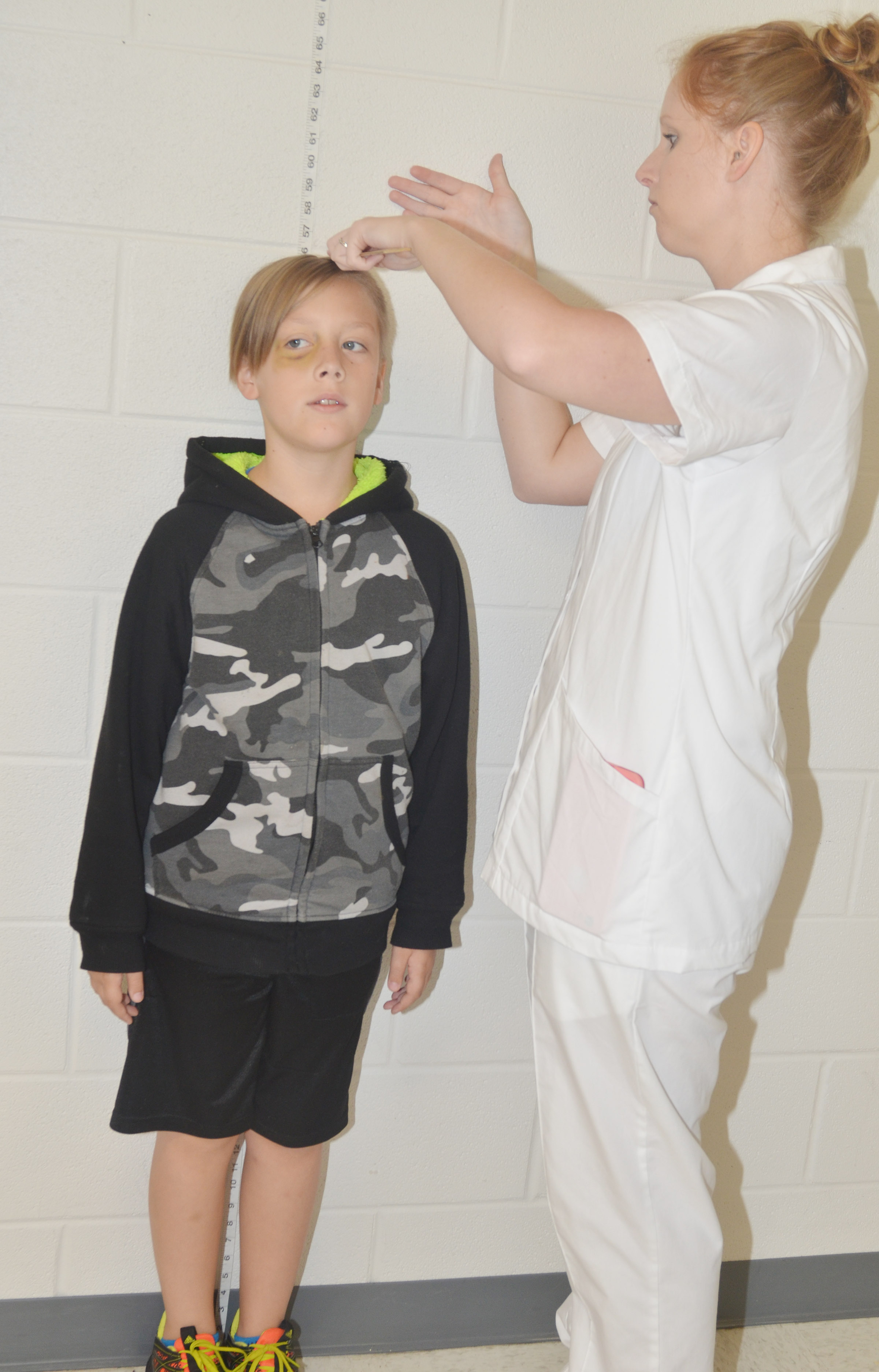CES fourth-grader Izak Burress has his height measured by Campbellsville University nursing student Danielle Hundley.