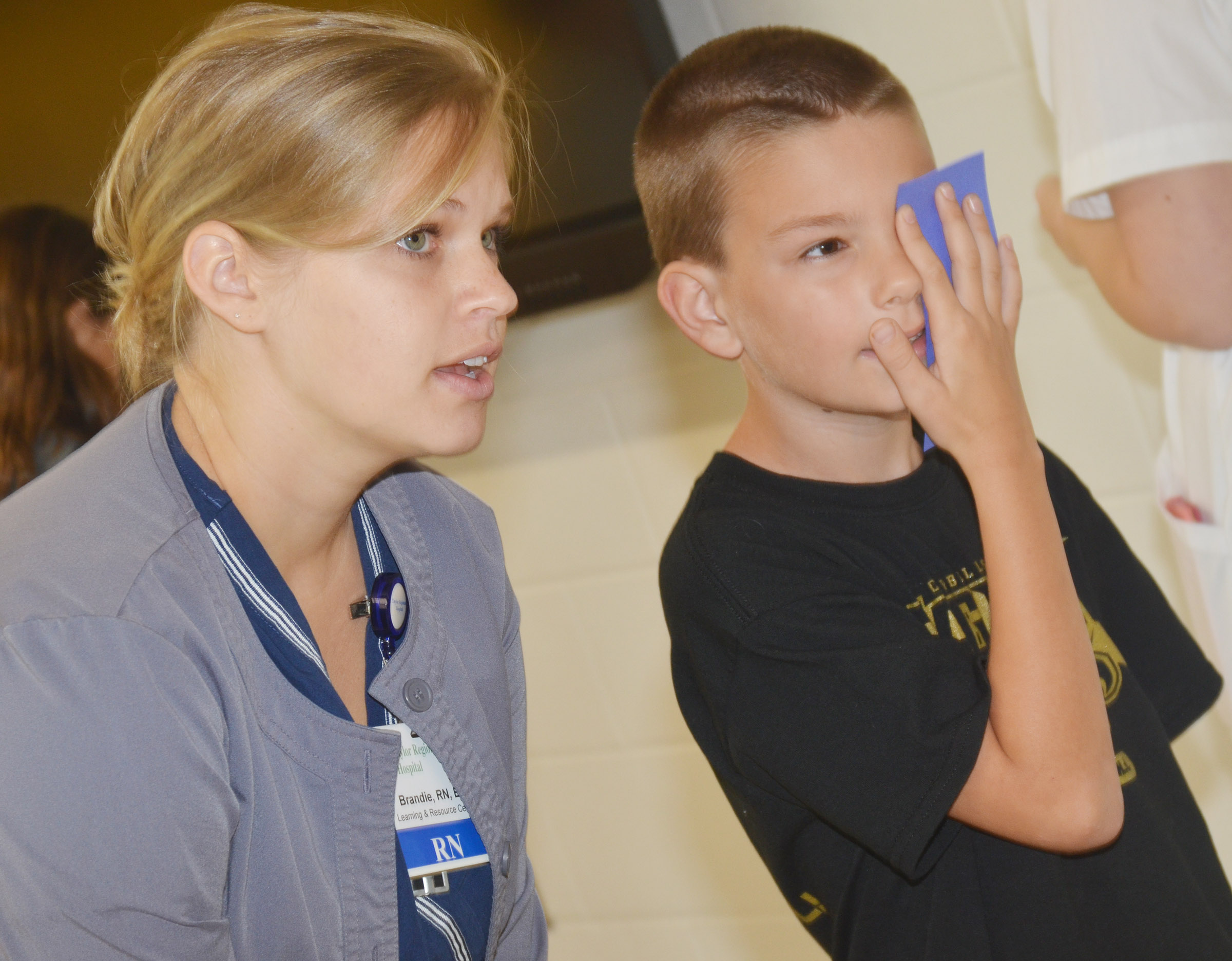 CES fifth-grader Taylan Hunt undergoes an eye exam with Brandie Adams, a registered nurse at Taylor Regional Hospital.