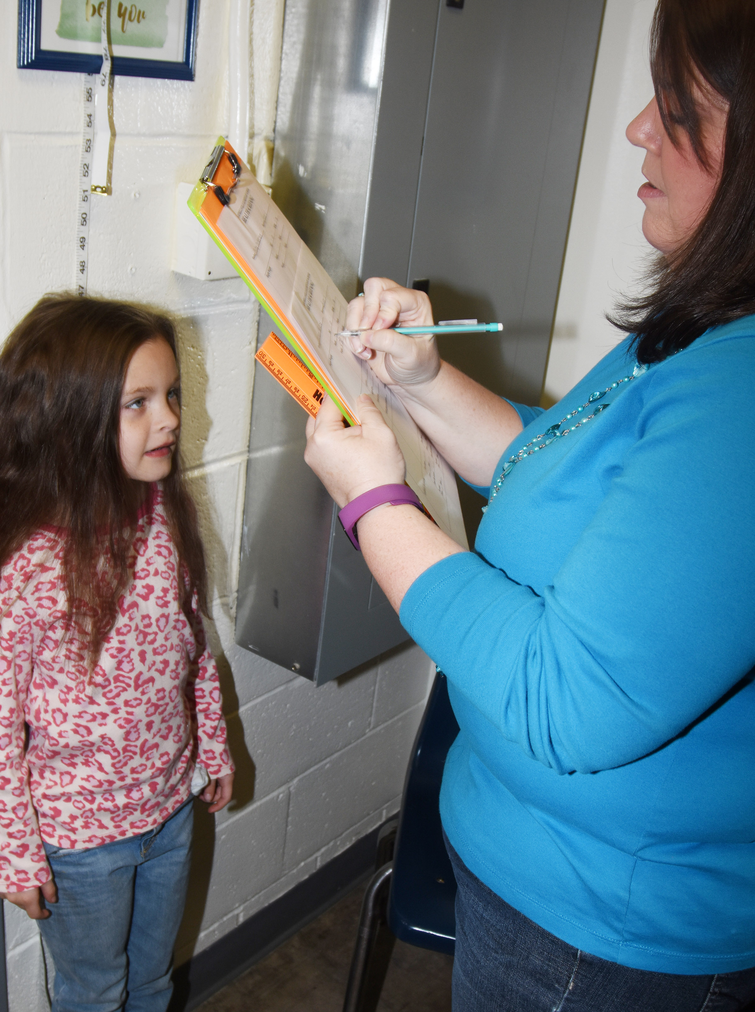 CES Guidance Counselor Beth Wiedewitsch measures first-grader Addison Perkins to see how much she has grown.