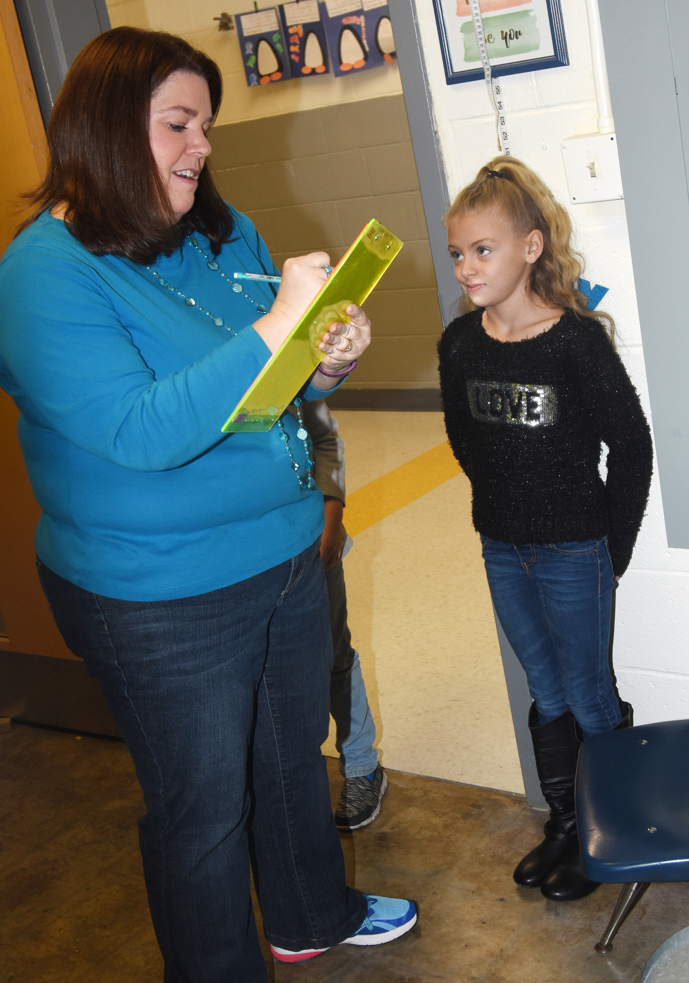 CES Guidance Counselor Beth Wiedewitsch measures first-grader Aliyah Litsey to see how much she has grown.