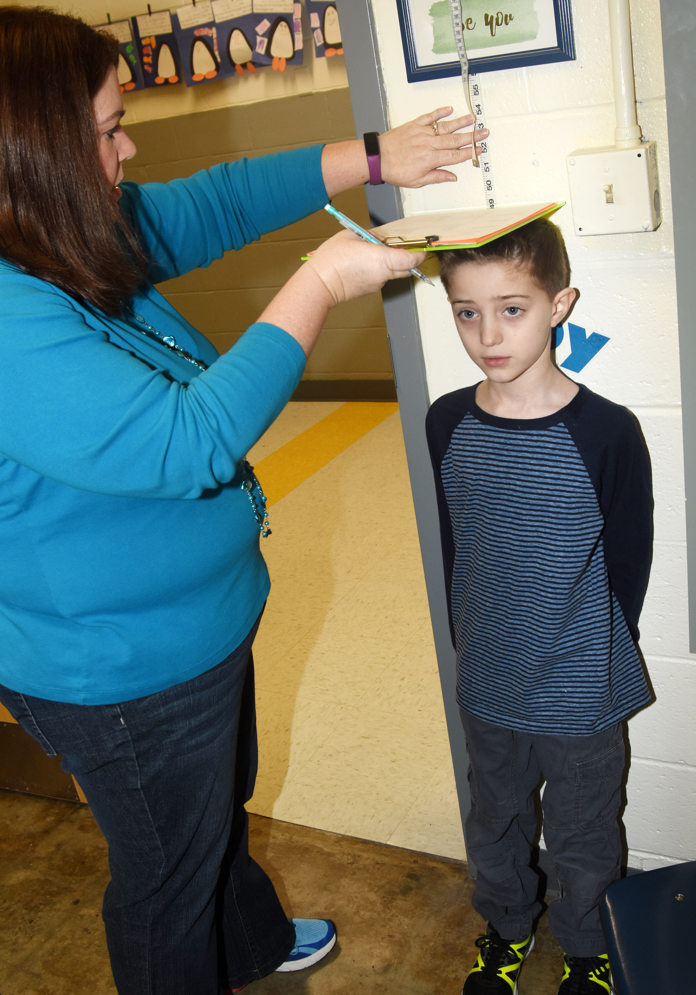 CES Guidance Counselor Beth Wiedewitsch measures first-grader Caleb Goodson to see how much he has grown.