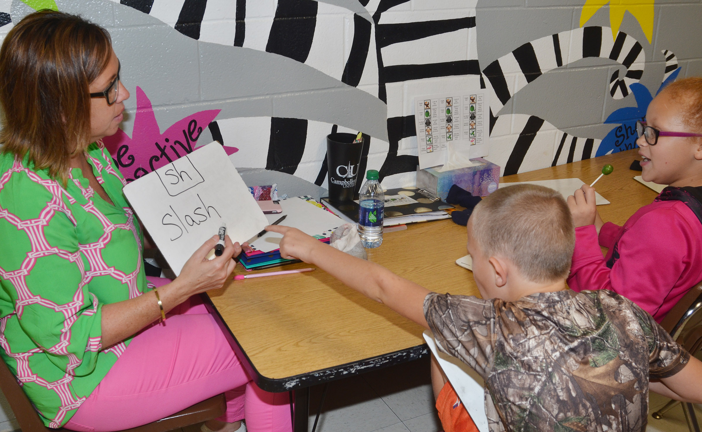 "CES writing interventionist Farrah Hord works with third-graders Tyler Brown, at left, and Kallie Taylor to write words that contain ""sh."""