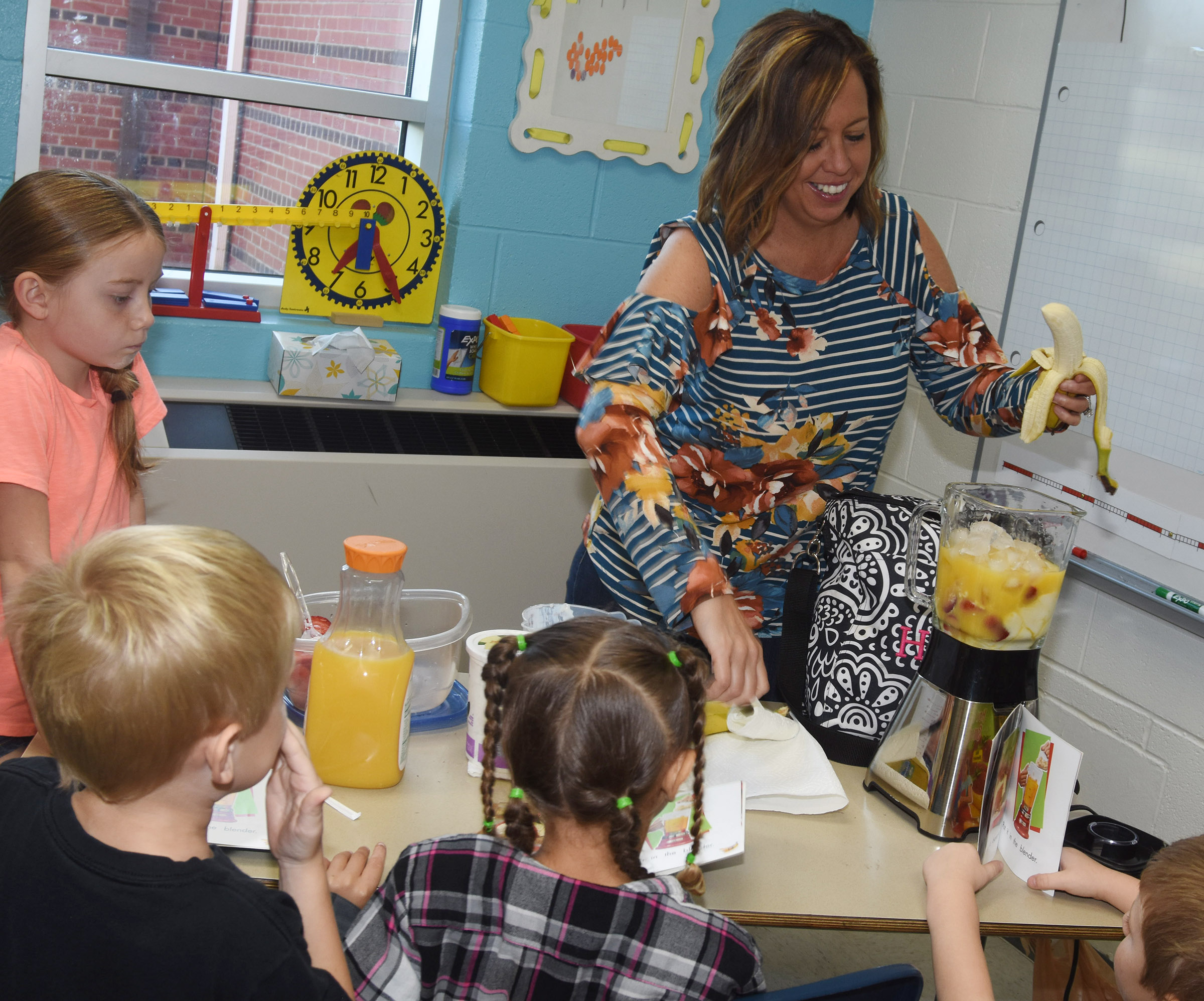 CES reading interventionist Farrah Hord adds a banana as she and her first-grade students read how to make a smoothie. Pictured are, from left, Courtney Gilbert, Carsen Montgomery and Fallyn Smith.