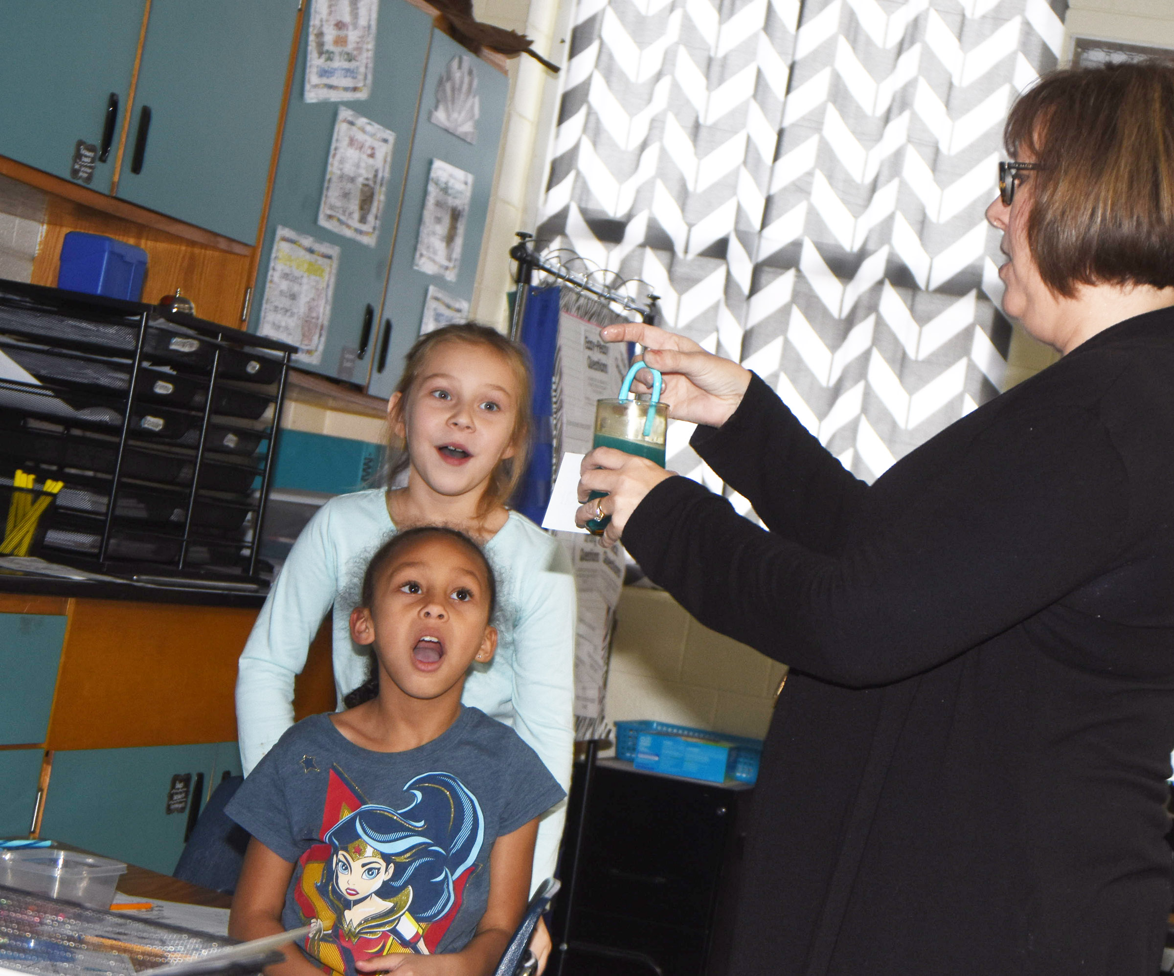 CES second-grade teacher Lynne Horn places a candy cane in vinegar to show her students the reaction. Pictured are Elyzabeth Fisher, in front, and Kira Dotson.