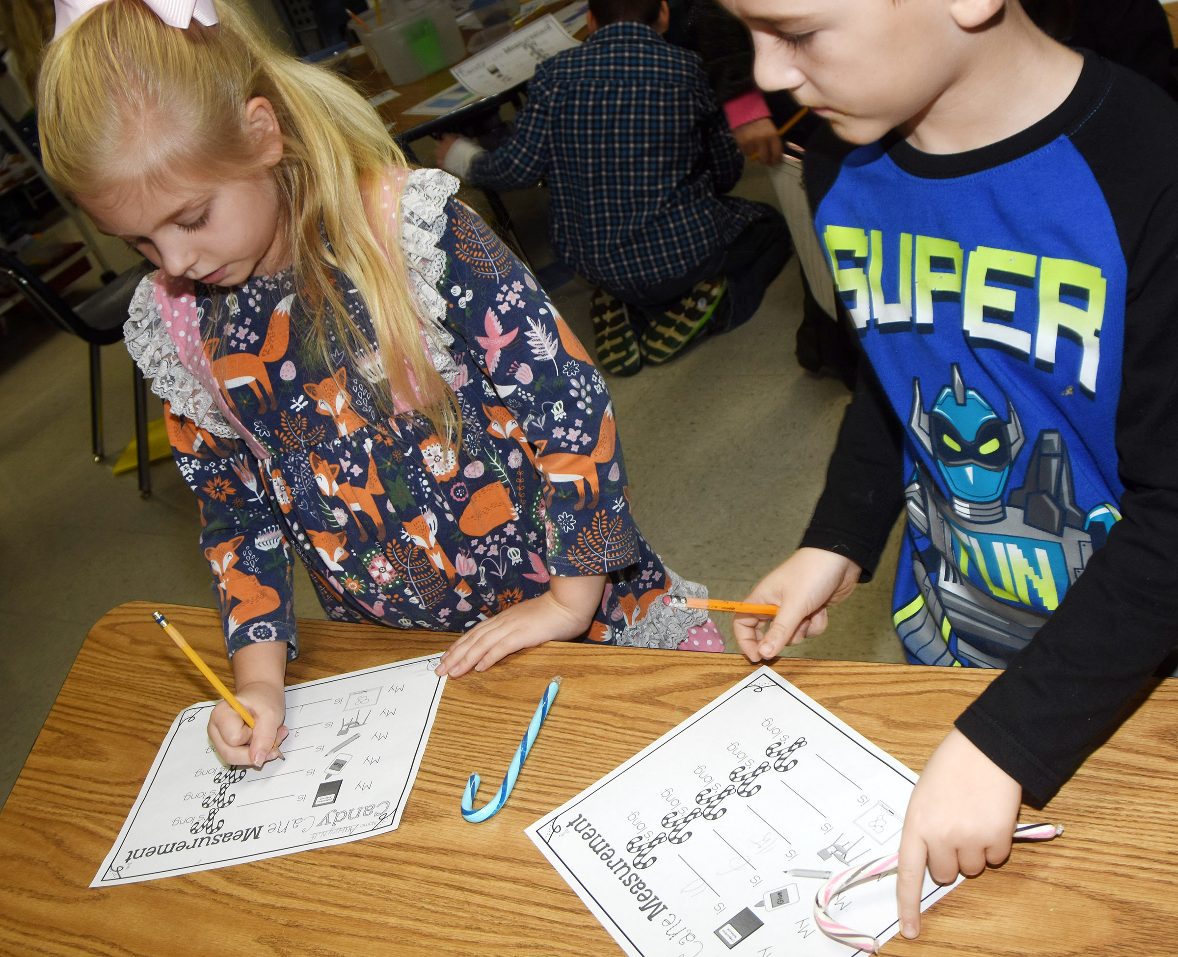 CES second-graders Aubrey Novak, at left, and Mason Edwards use their candy canes to measure objects in their classroom.