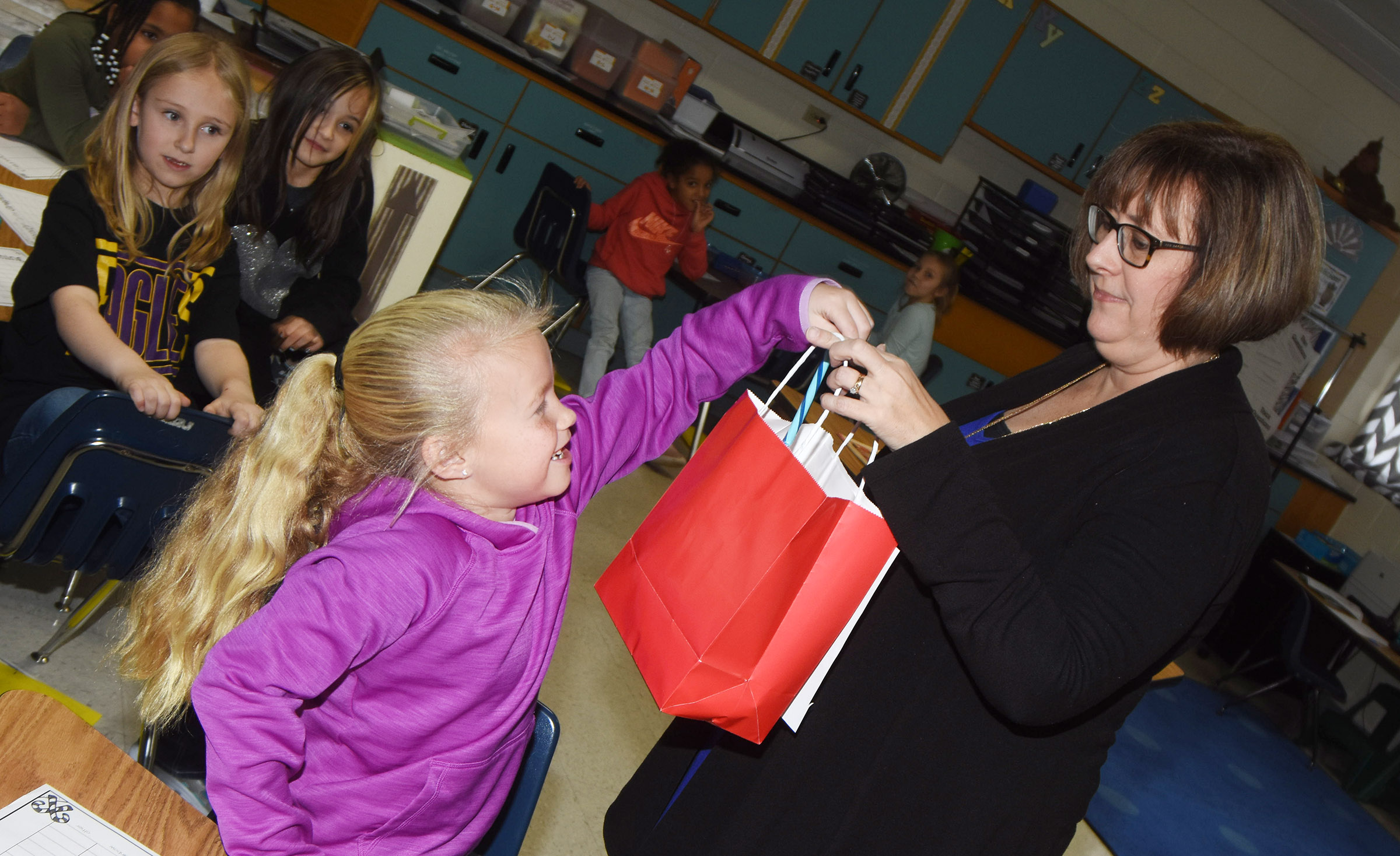 CES second-grader Lillie Judd chooses a candy cane from teacher Lynne Horn's bag.