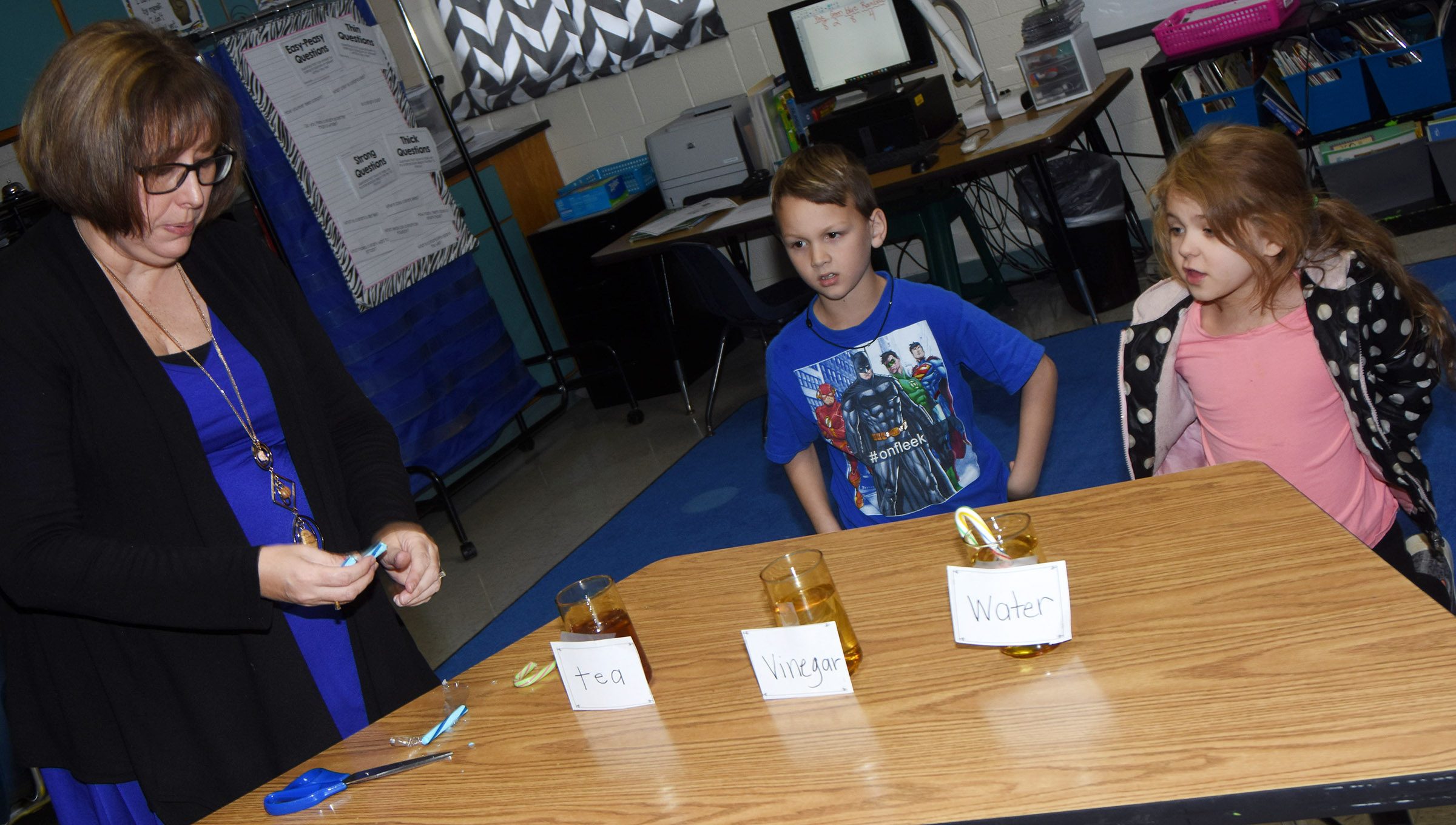 CES second-grade teacher Lynne Horn places candy canes in tea, vinegar and water for her students to observe the chemical reactions. Pictured are Justice Nelson and Aubrey Wilson.