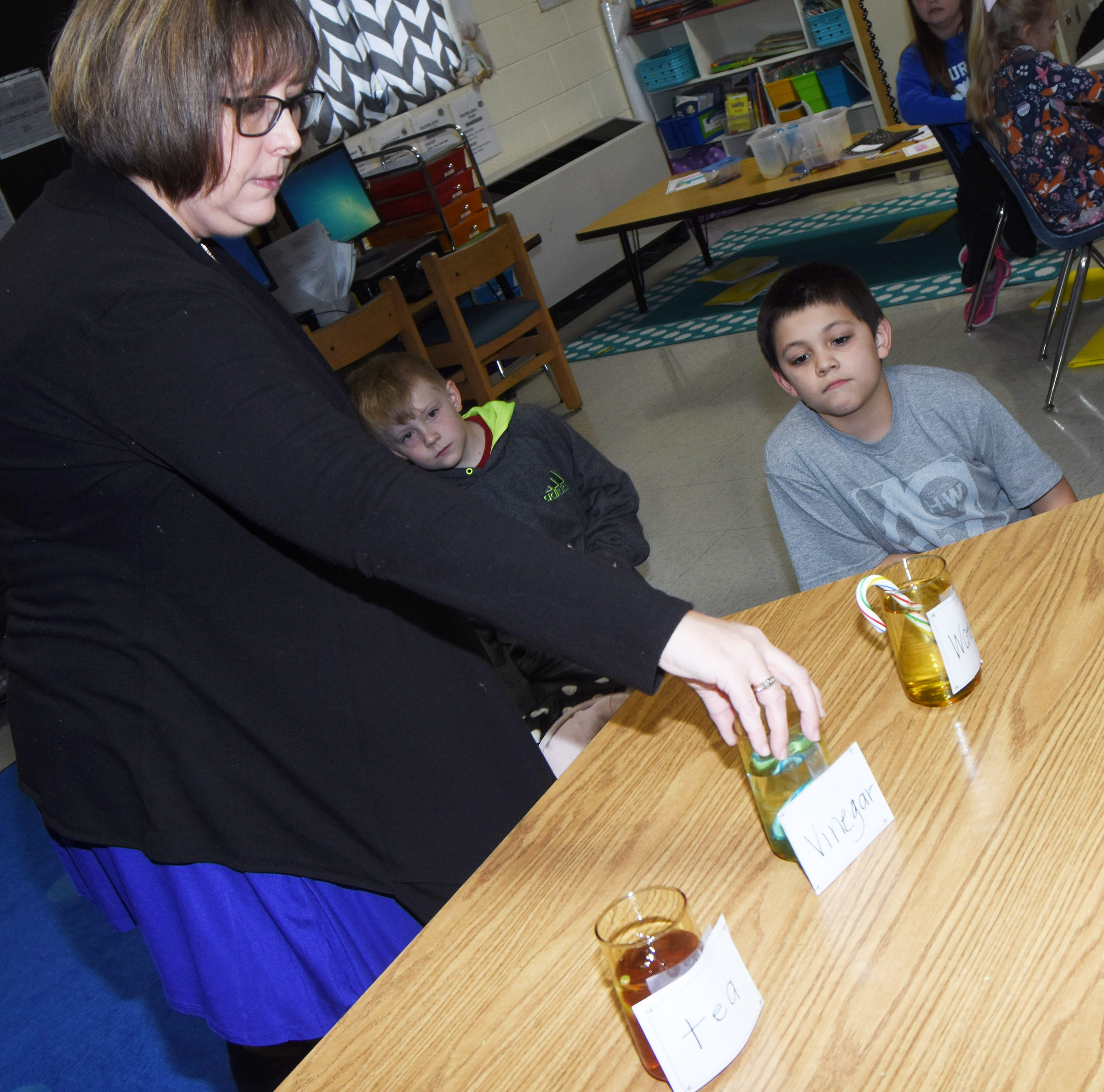 CES second-grade teacher Lynne Horn places candy canes in tea, vinegar and water for her students to observe the chemical reactions. Pictured are Gage Henderson, center, and Keagan Shearer.