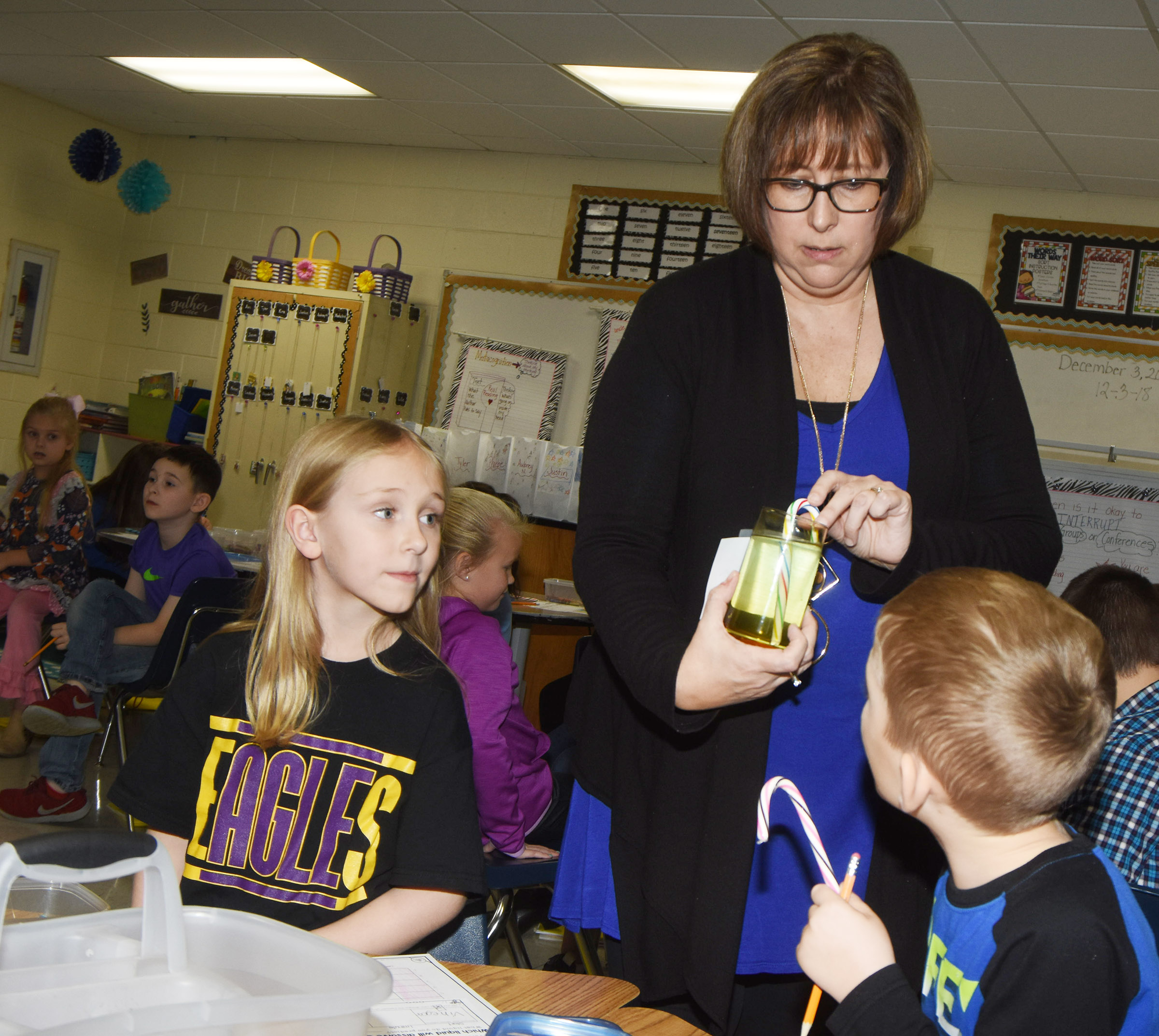CES second-grade teacher Lynne Horn shows her students a candy cane in water to observe the reaction. Pictured are LeeAnna Garvin and Mason Edwards.