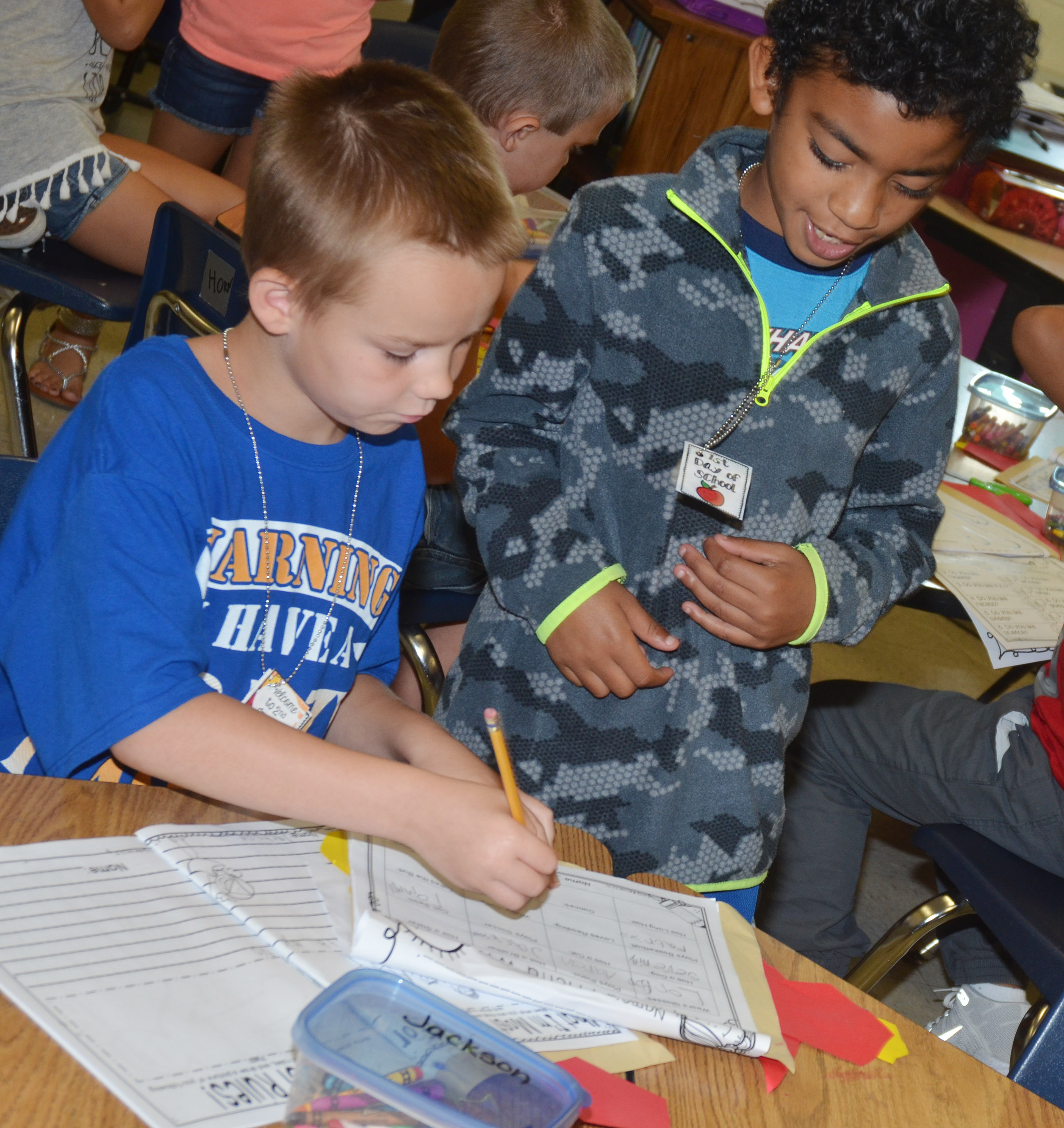 CES second-graders Jackson Bates, at left, and Enoch Smith sign each other's worksheets as they get to know each other.