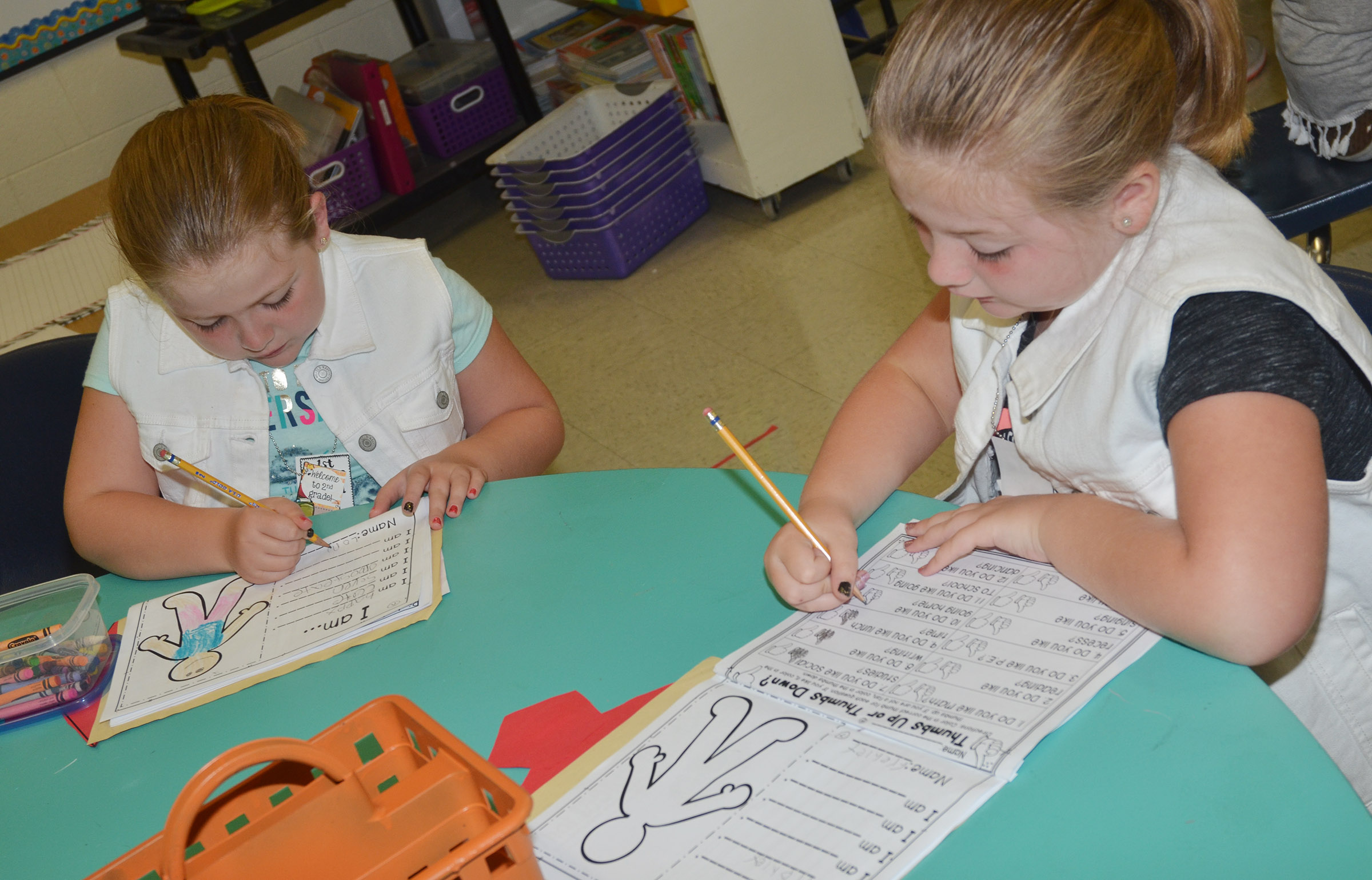 CES second-graders London Whitlow, at left, and Frehley Whitlow write in their booklets about themselves.