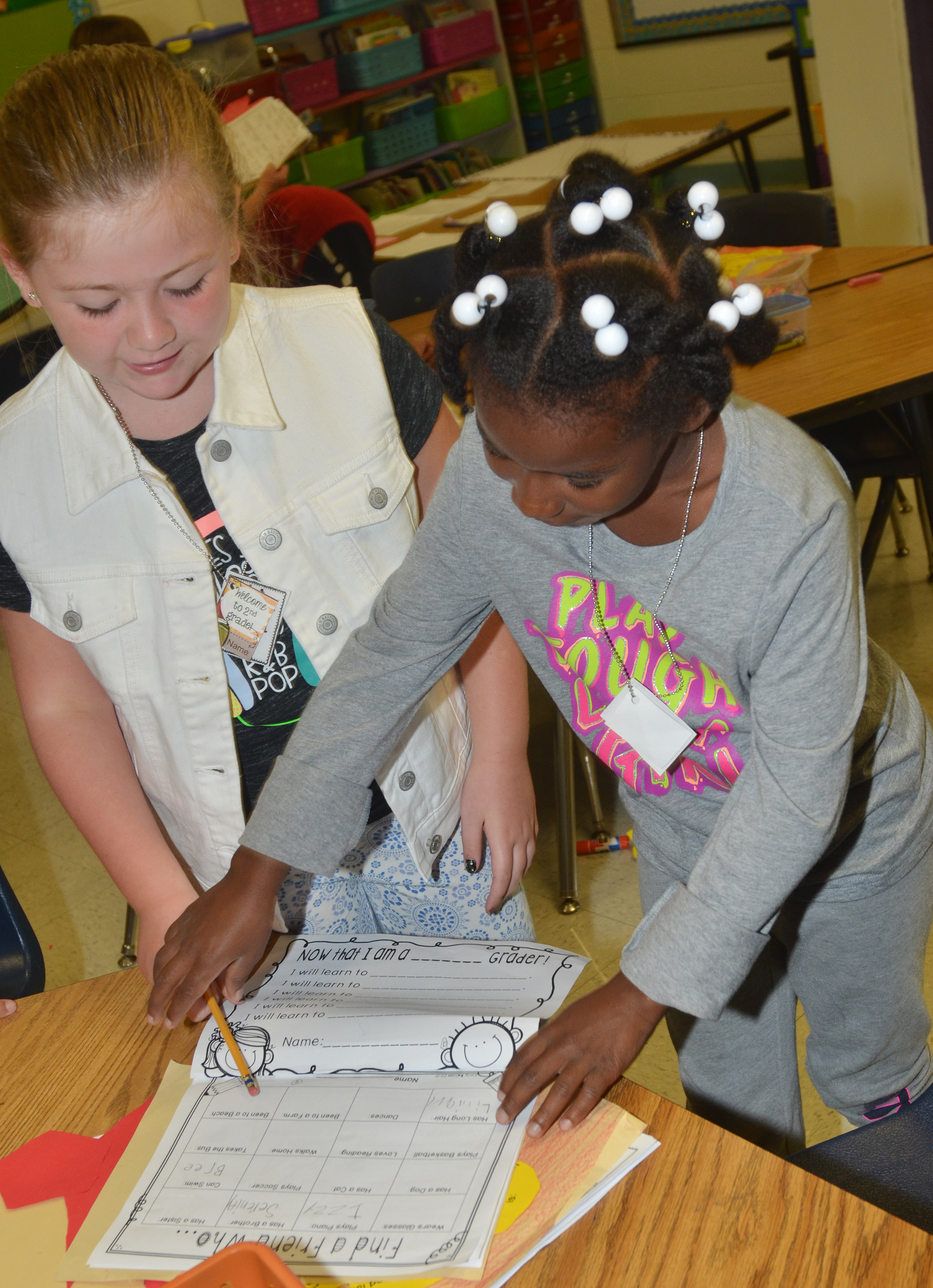 CES second-graders Frehley Whitlow, at left, and Destini Gholston sign each other's worksheets as they get to know each other.