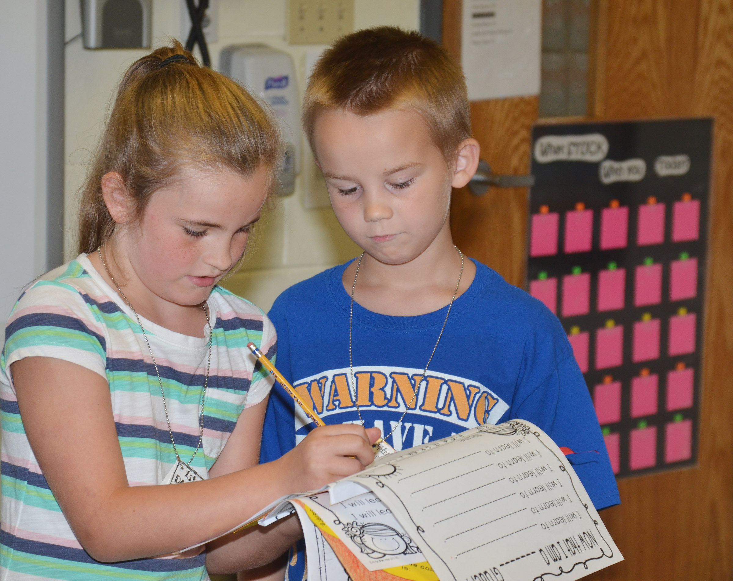 CES second-graders Bree Farmer, at left, and Jackson Bates sign each other's worksheets as they get to know each other.