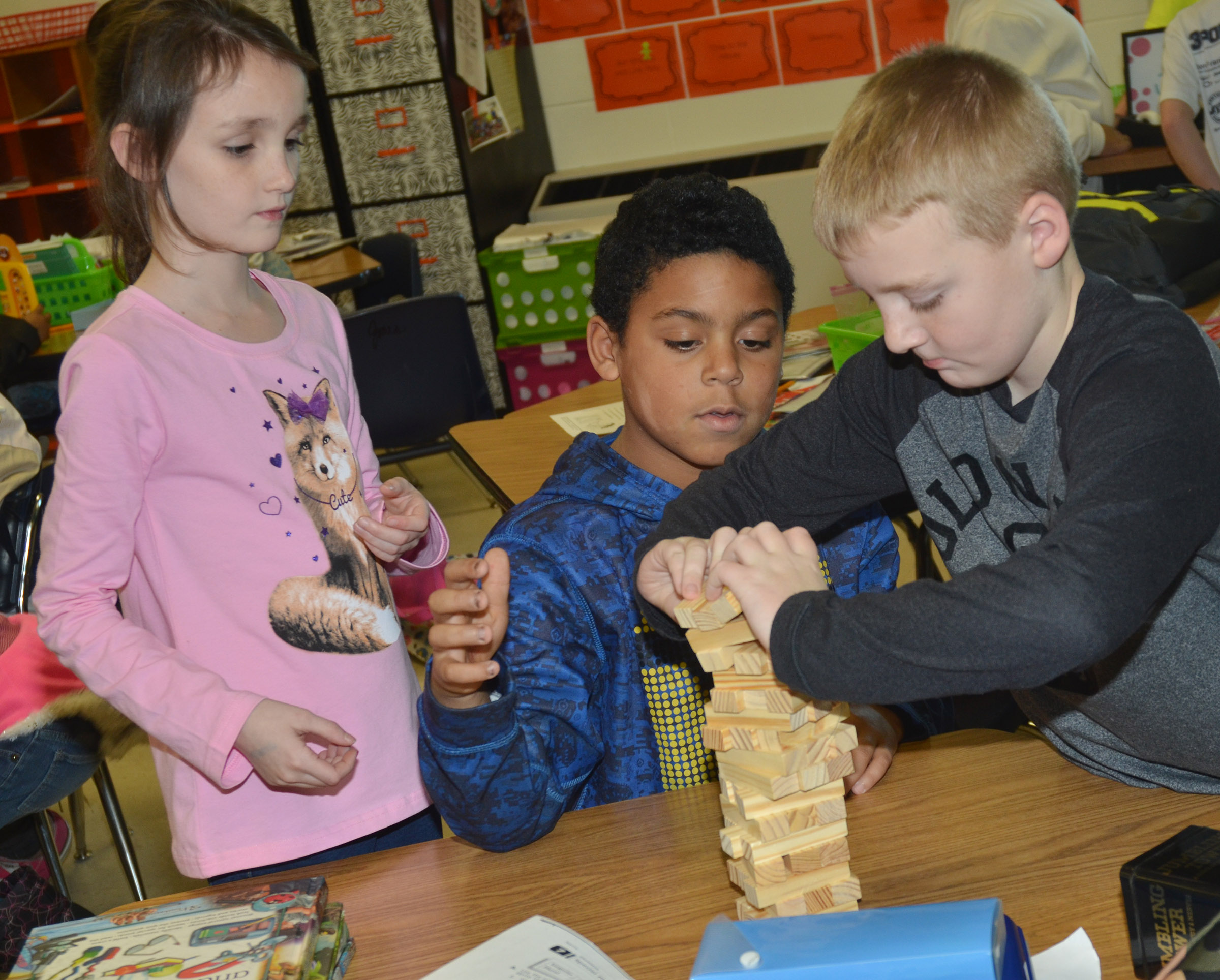 CES third-graders, from left, Paige Ritchie, Bryson Groves and Ryder Murphy play Jenga.
