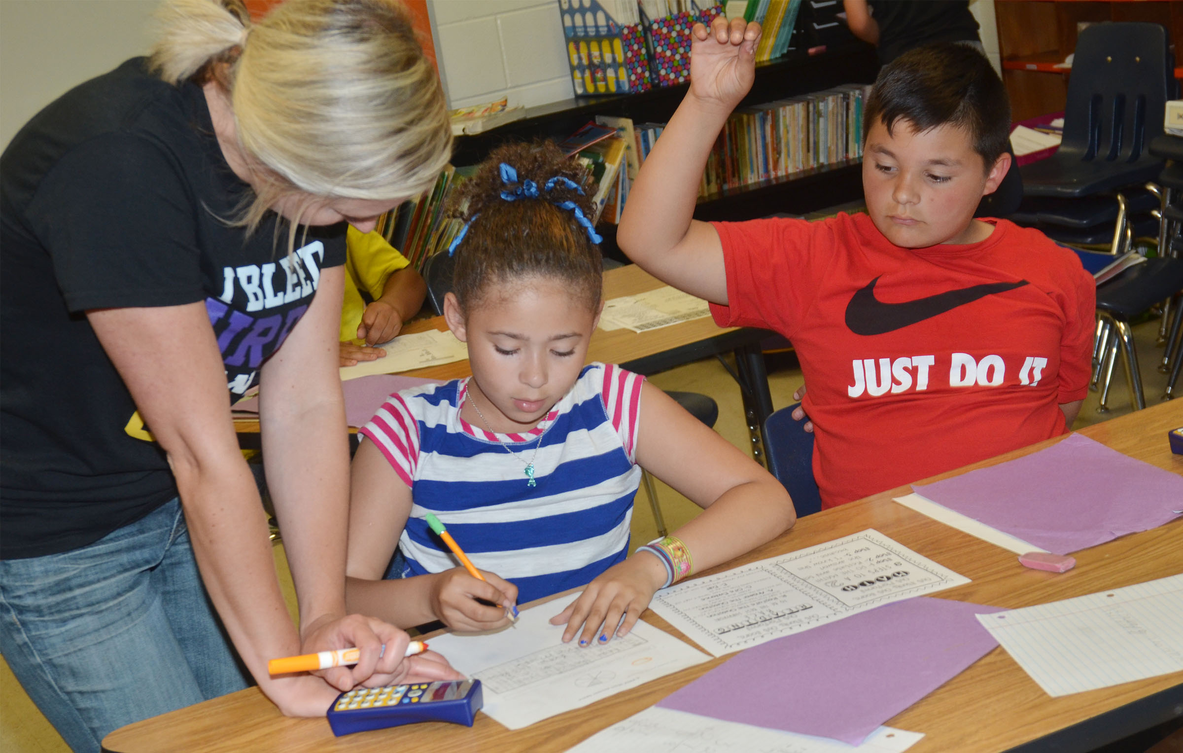 CES third-grade teacher Hannah Jones helps Rihanna Anderson and Brayden Paiz with a sample test question.