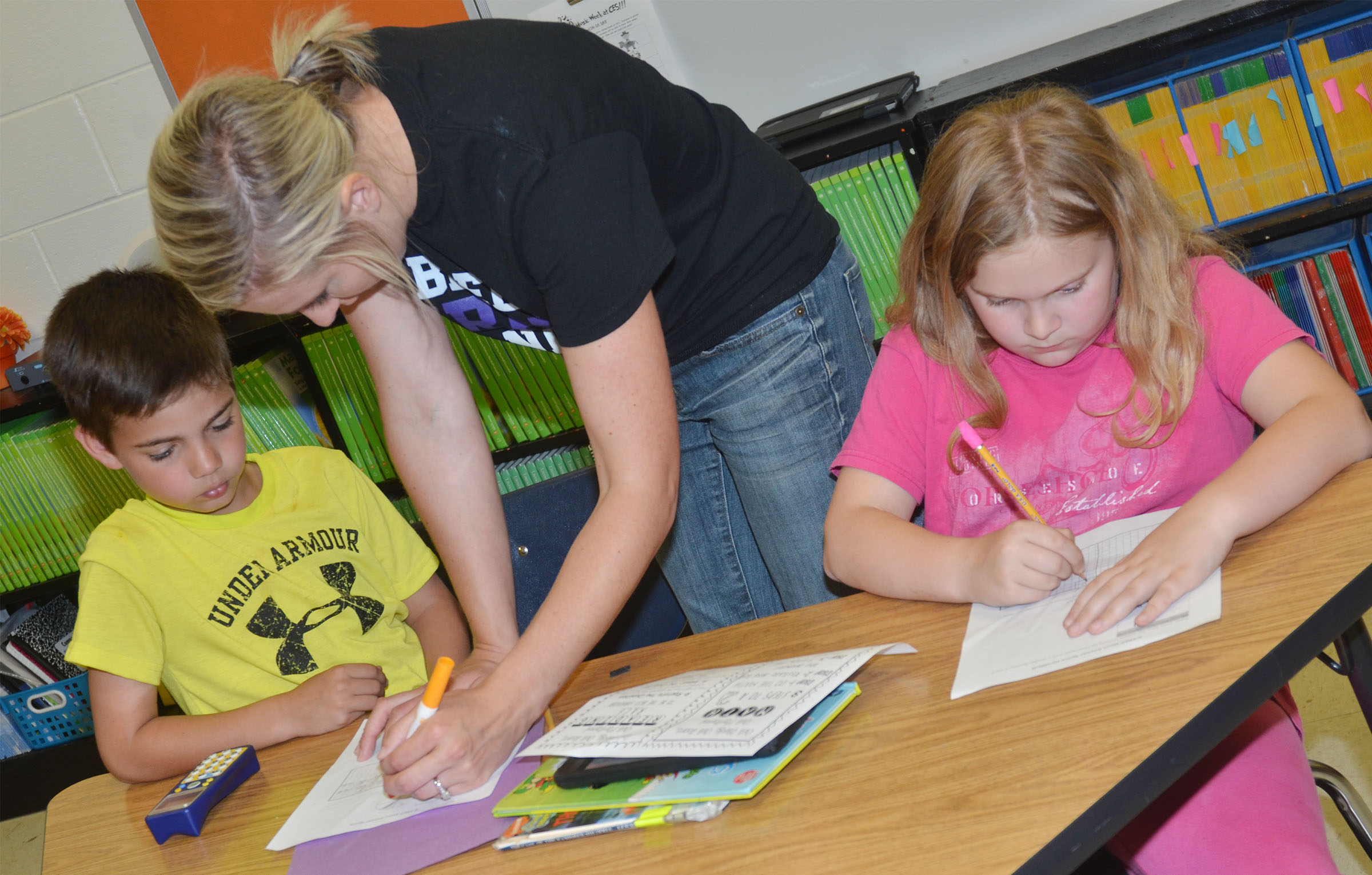 CES third-grade teacher Hannah Jones helps Easton Williams, at left, and Arianna Childers with a sample test question.
