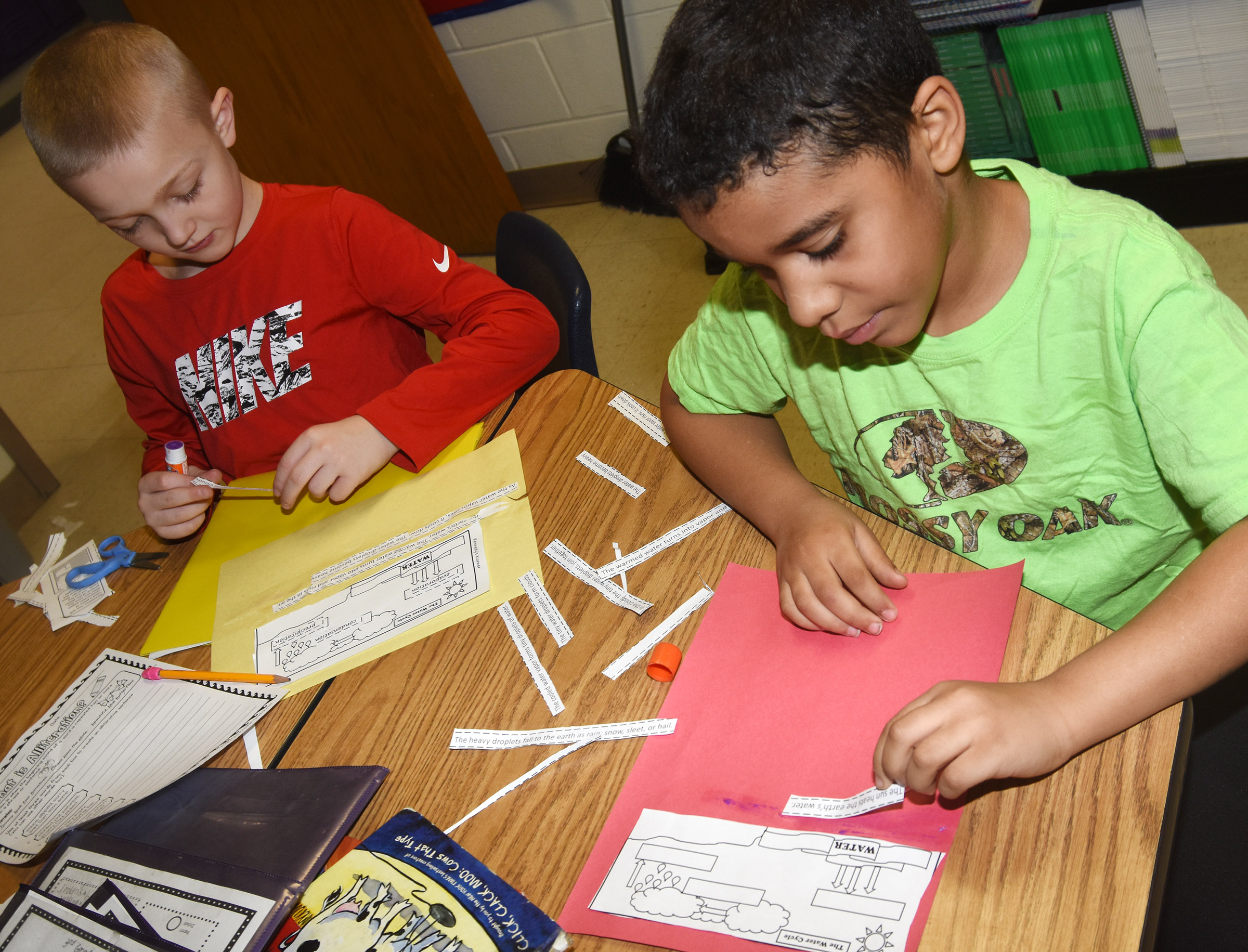CES third-graders Trenton Harris, at left, and Christopher Jolivert place the steps to the water cycle in order.