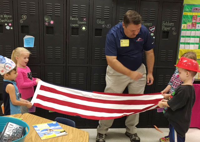 Dan Durham, program director at Air Evac Lifeteam and pastor at Stewarts Creek Baptist Church, shows CES kindergarteners how to fold the American flag.