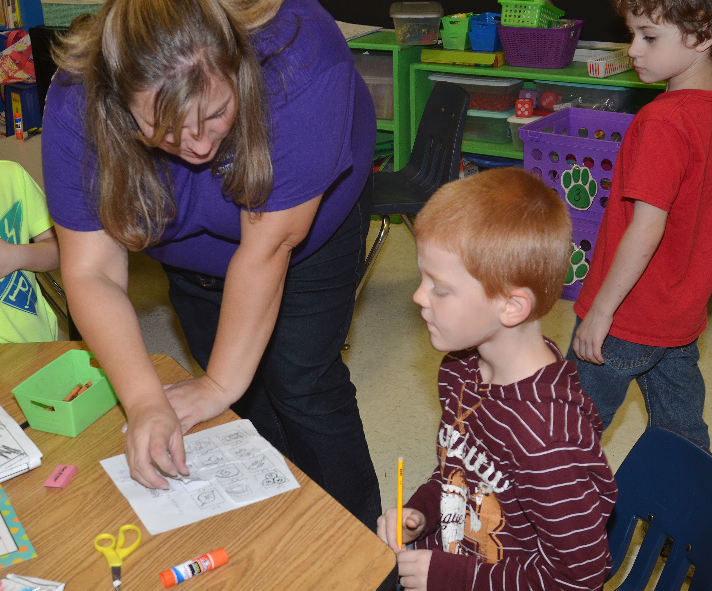 CES kindergarten teacher Kimberly Clark helps Cambrien Couch complete his animal life cycle worksheet.