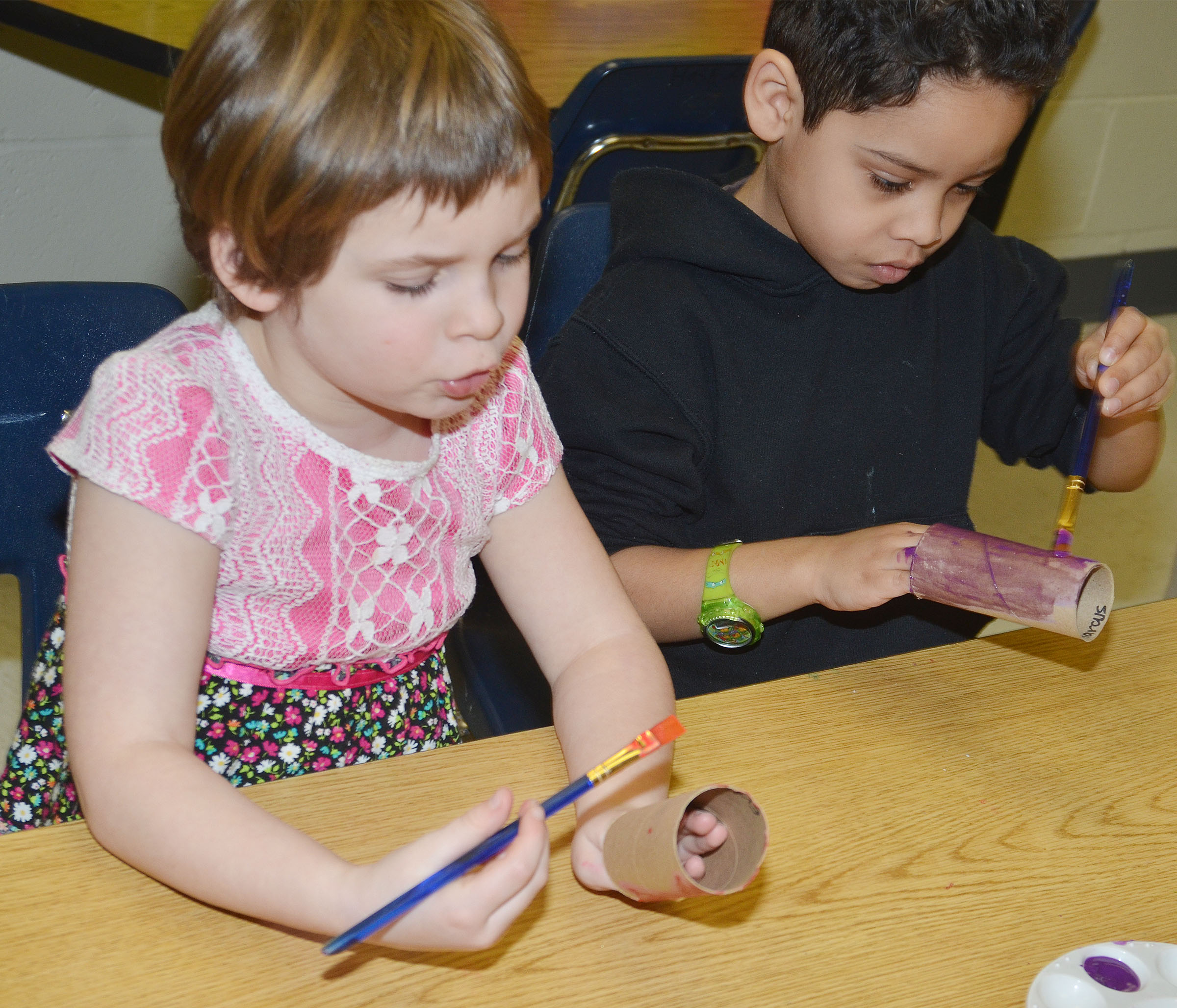 CES kindergarteners Evelyn Reed, at left, and Demarcus Noyola paint their toilet paper rolls.